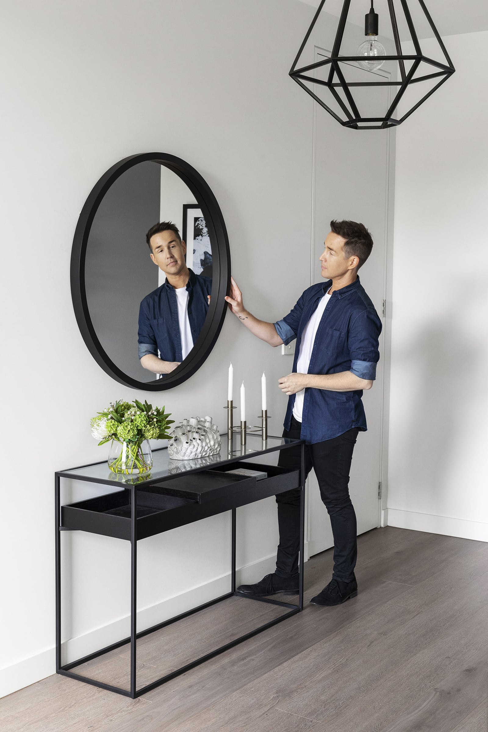 black round mirror in entryway above black and glass top console table from calibre furniture