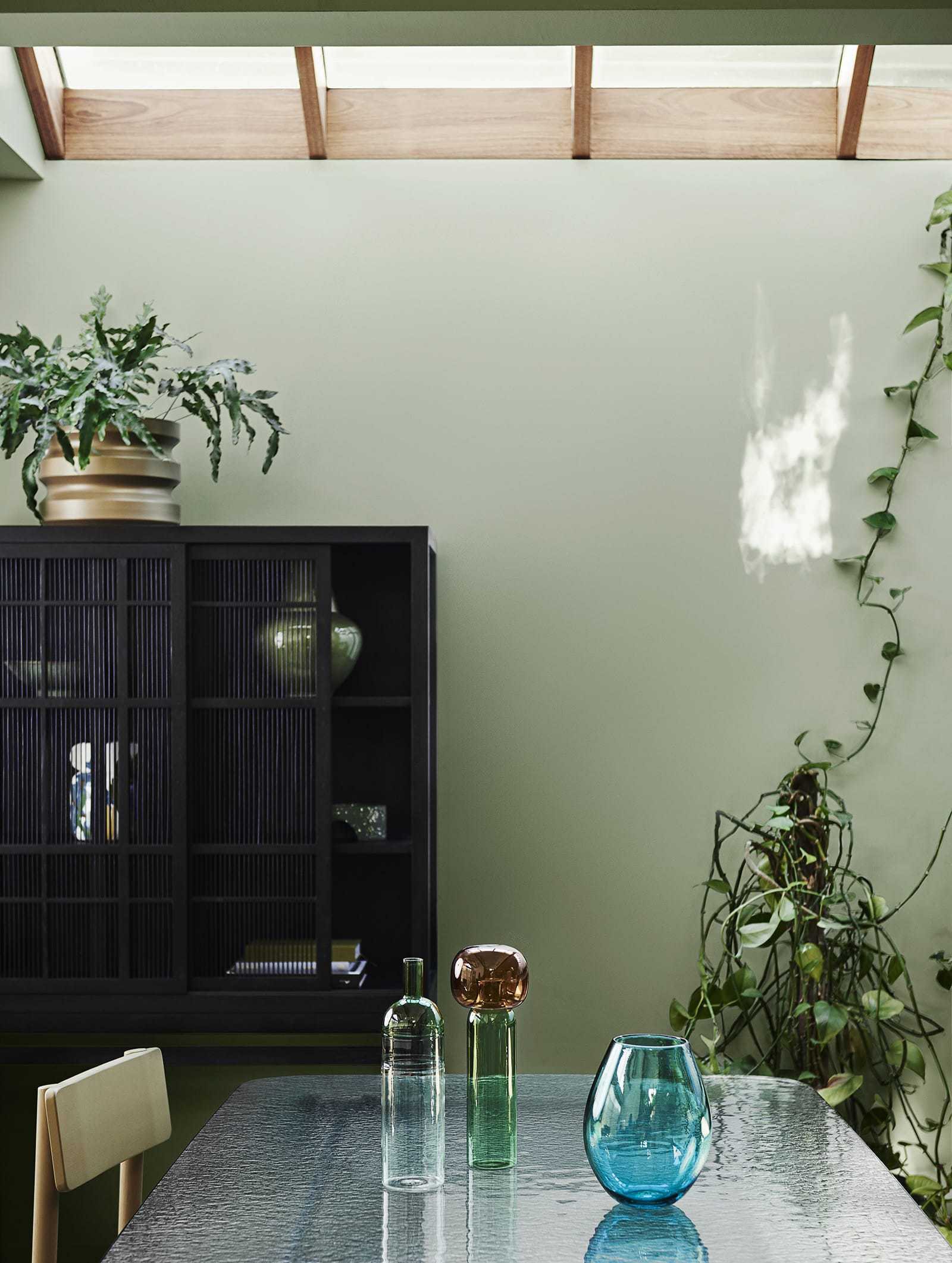dulux light green paint feature wall in dining room with black storage unit