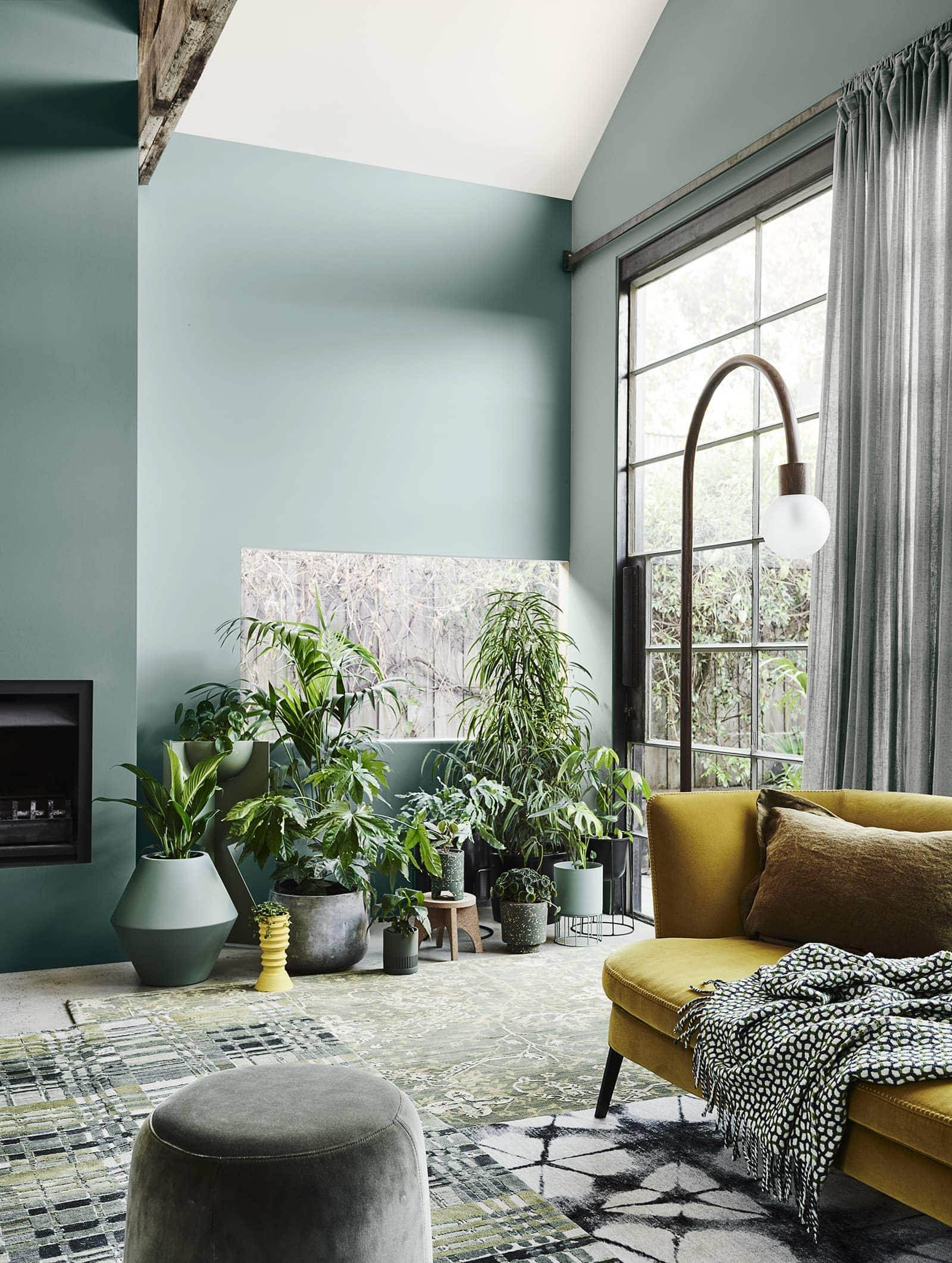 dulux light green painted living room with lots of indoor plants and mustard sofa