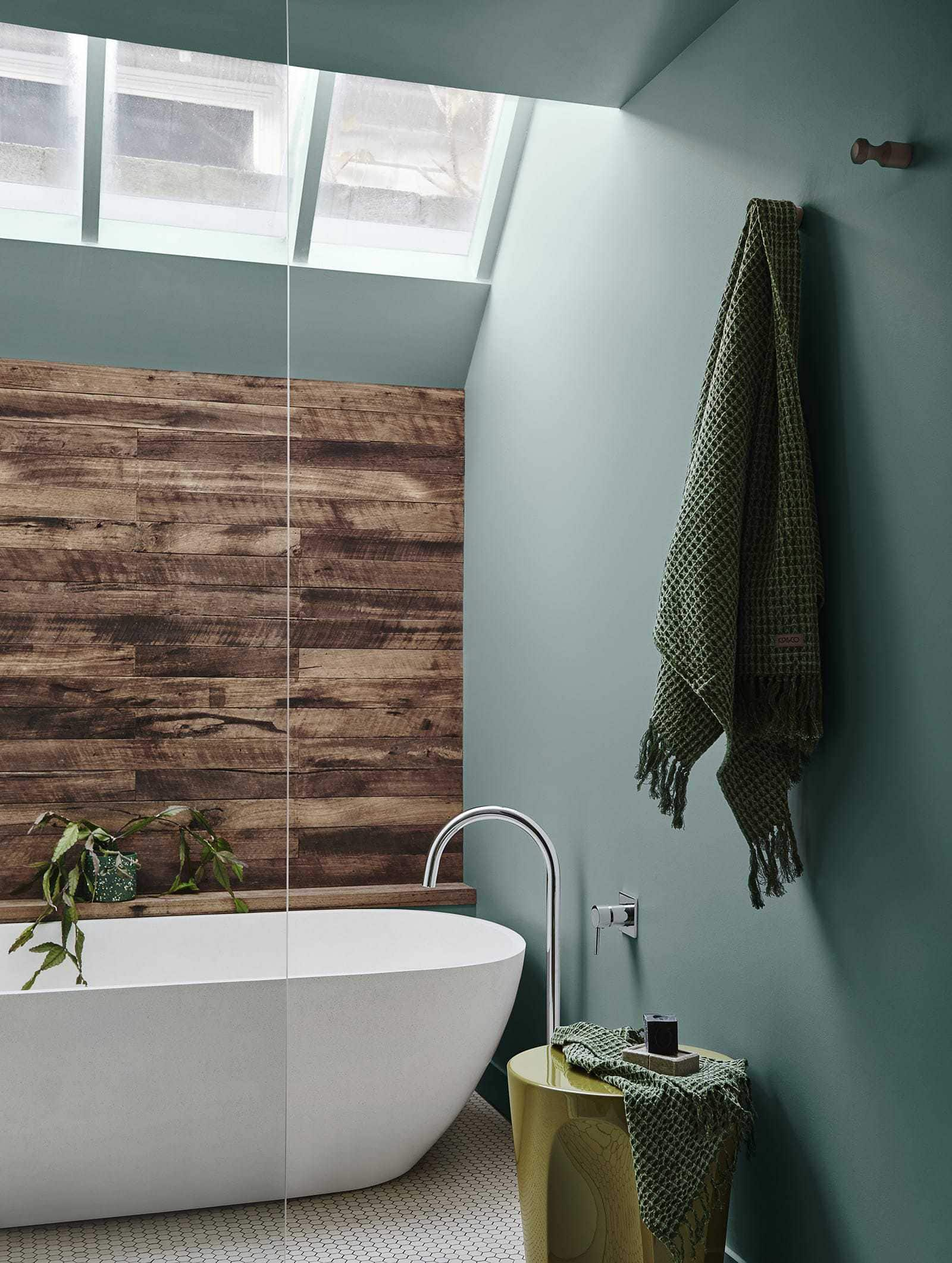 green bathroom with freestanding bath and timber panel wall