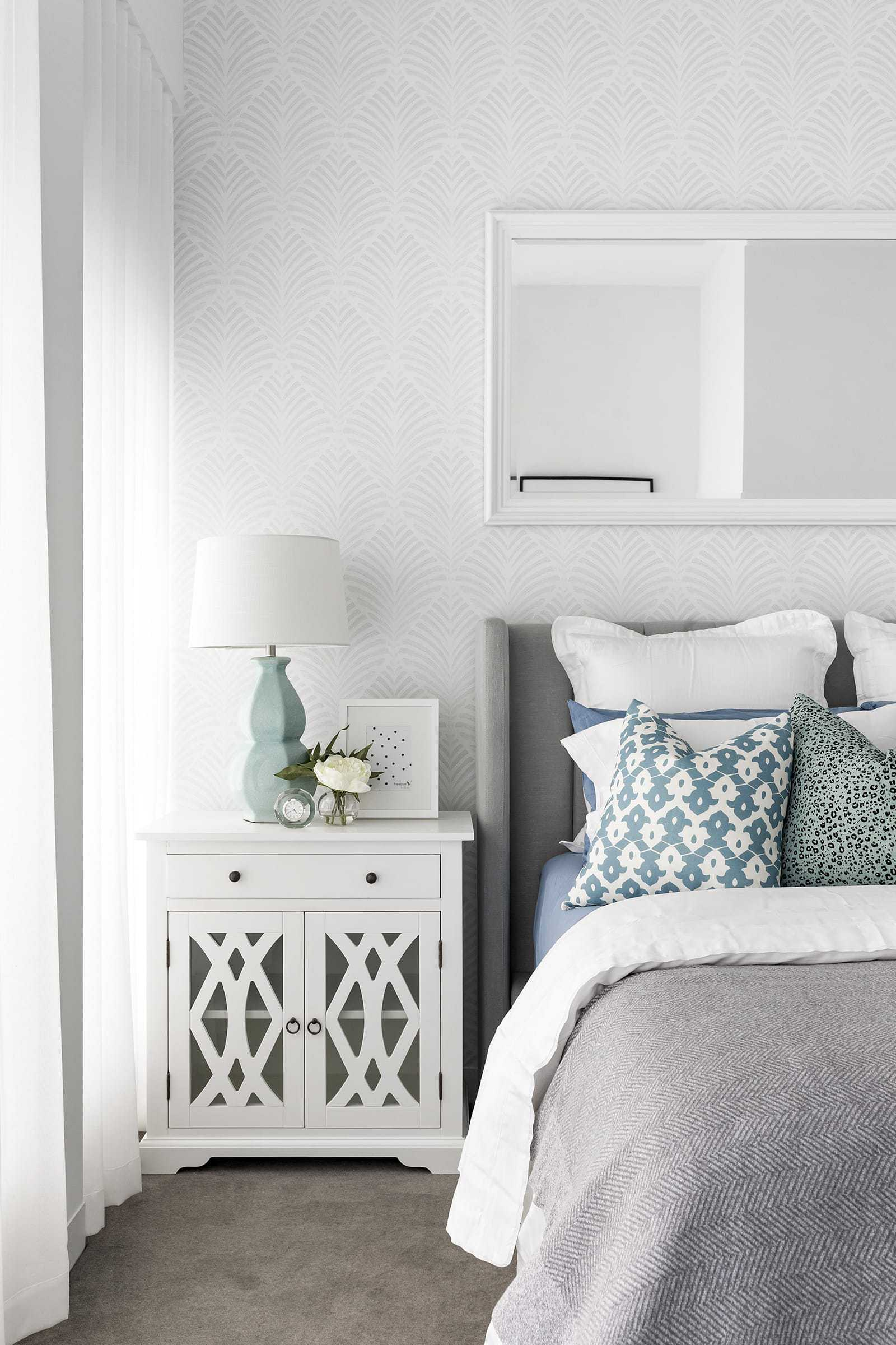 hamptons master bedroom with grey and white wallpaper and white bedside tables