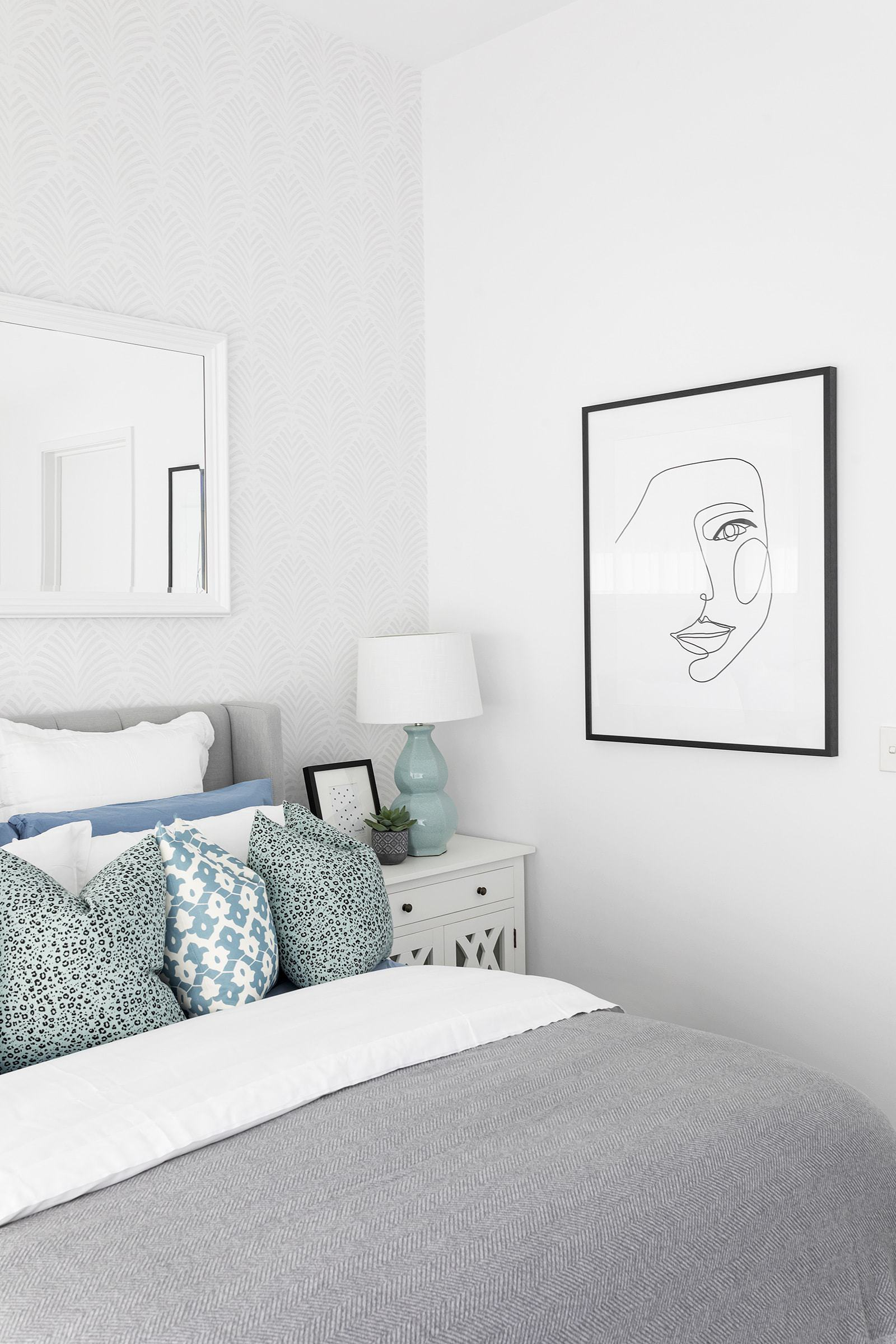 hamptons master bedroom with white bedside tables and blue and grey bedding
