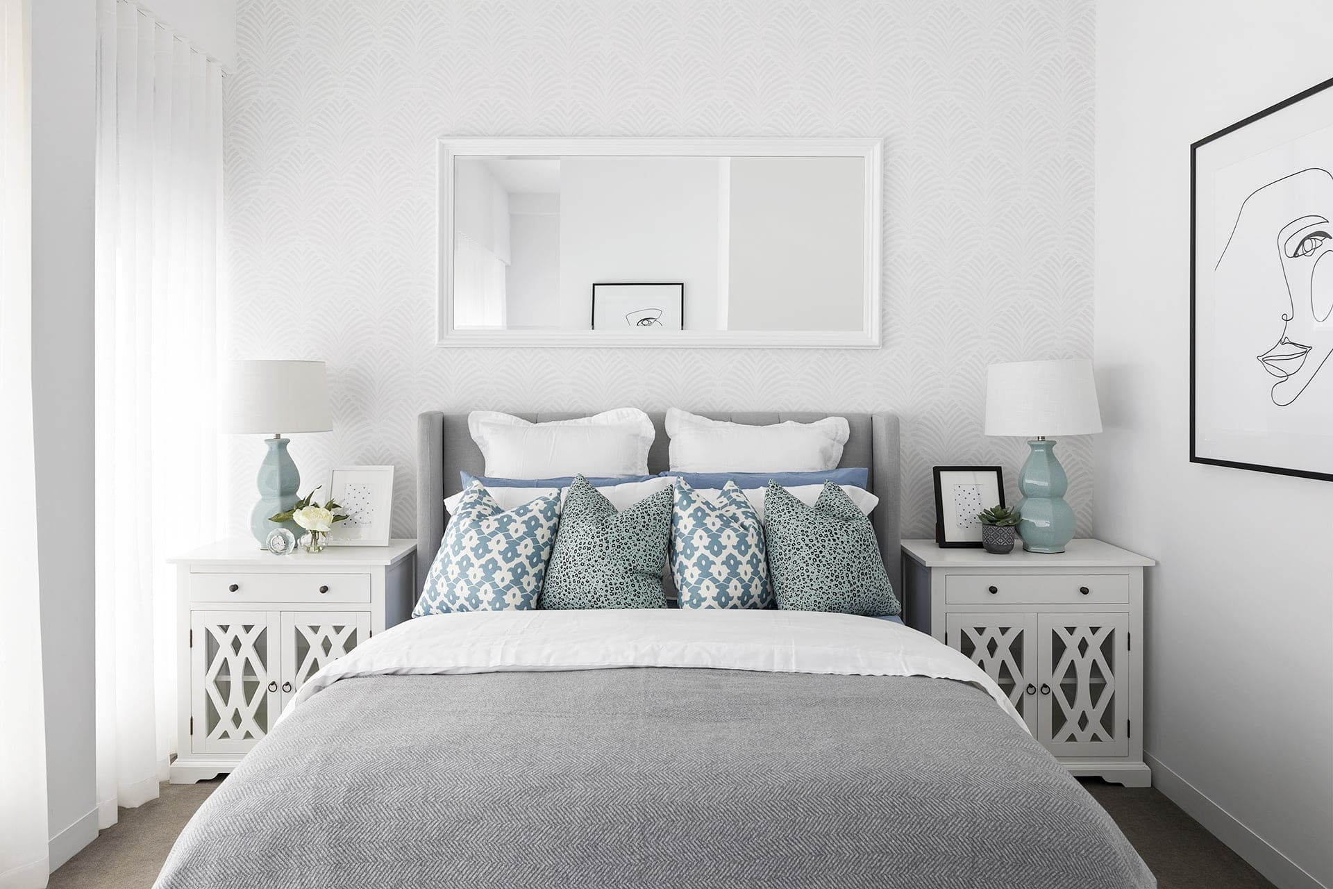 hamptons style master bedroom with white bedside tables and mirror above bed