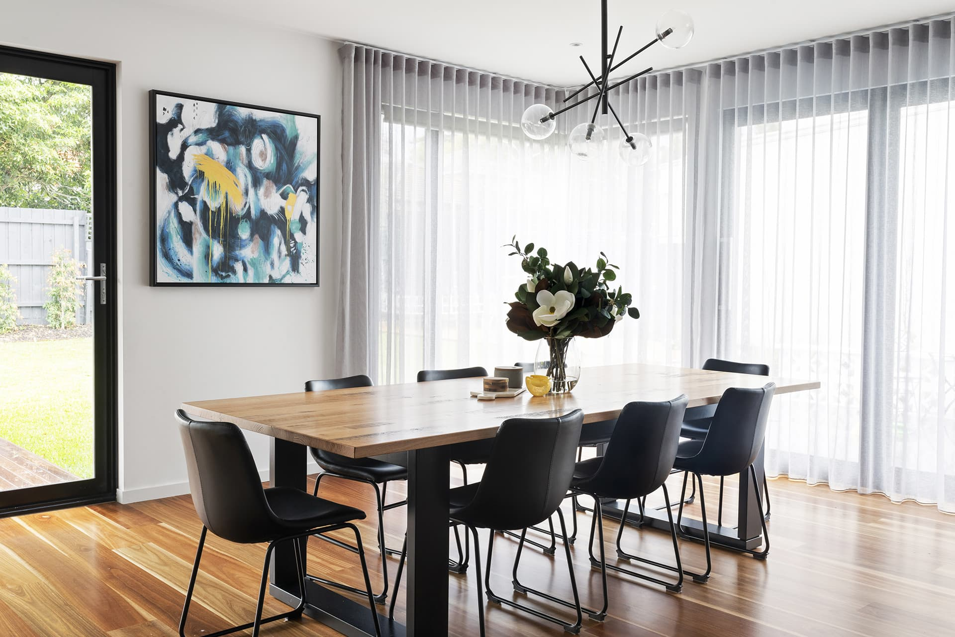 industrial dining table with australian natives and black leather dining chairs and sheer curtains