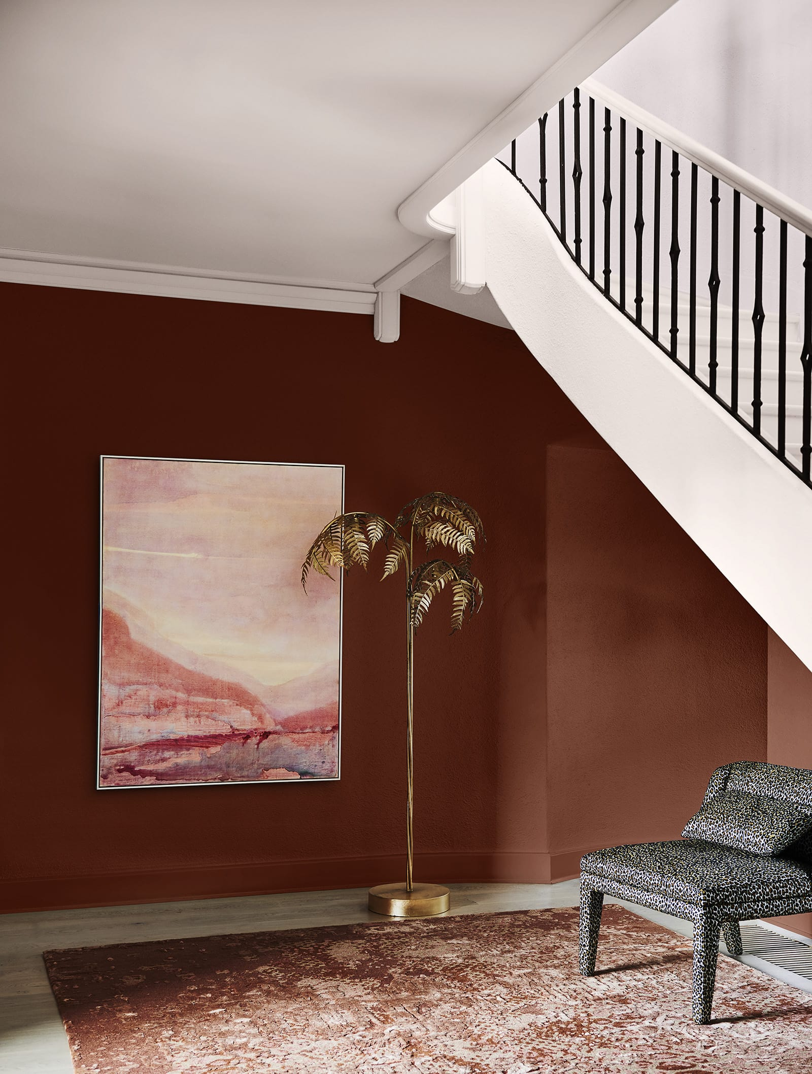 maroon feature wall in home with white staircase and gold palm statue dulux colour forecast