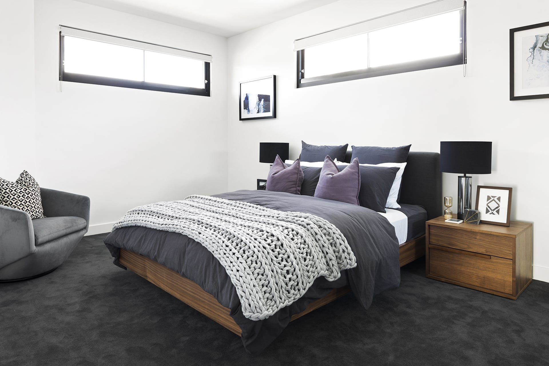 master bedroom with dark grey carpet brown timber bed and grey quilt cover set with purple cushions