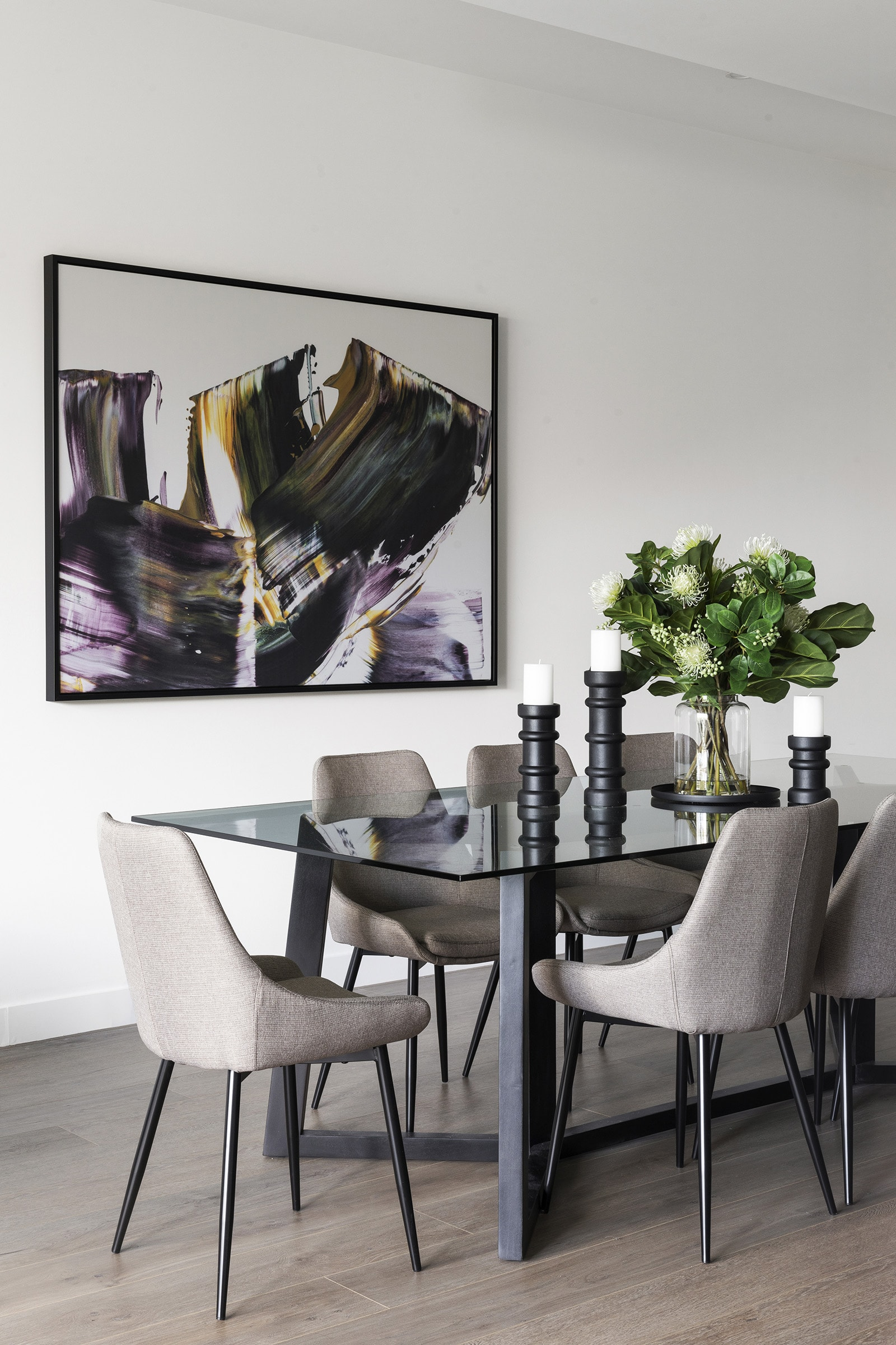 modern luxe dining room with glass top table grey upholstered chairs and fake flowers urban road wall art
