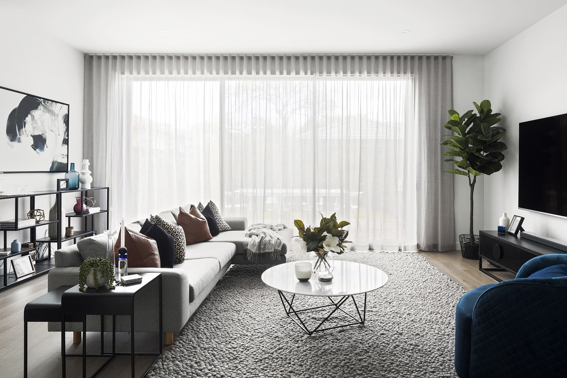 modern luxe living room with grey rug marble coffee table and sheer curtains