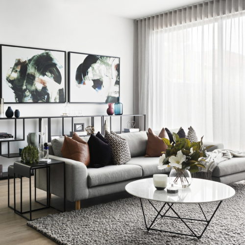 modern luxe living room with grey sofa tan leather cushions and marble coffee table