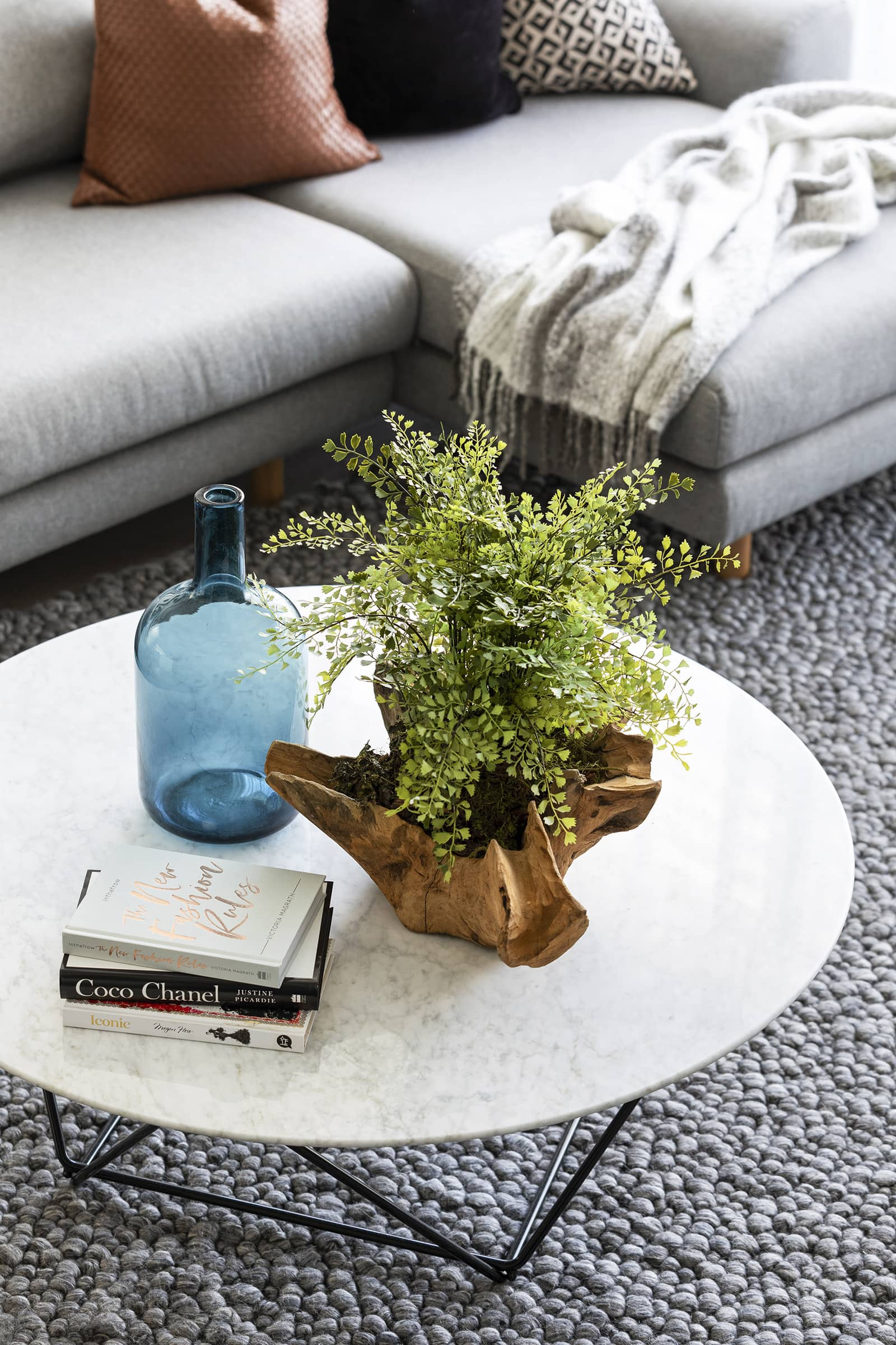 modern luxe living room with marble coffee table fake plant and blue glass vase from west elm