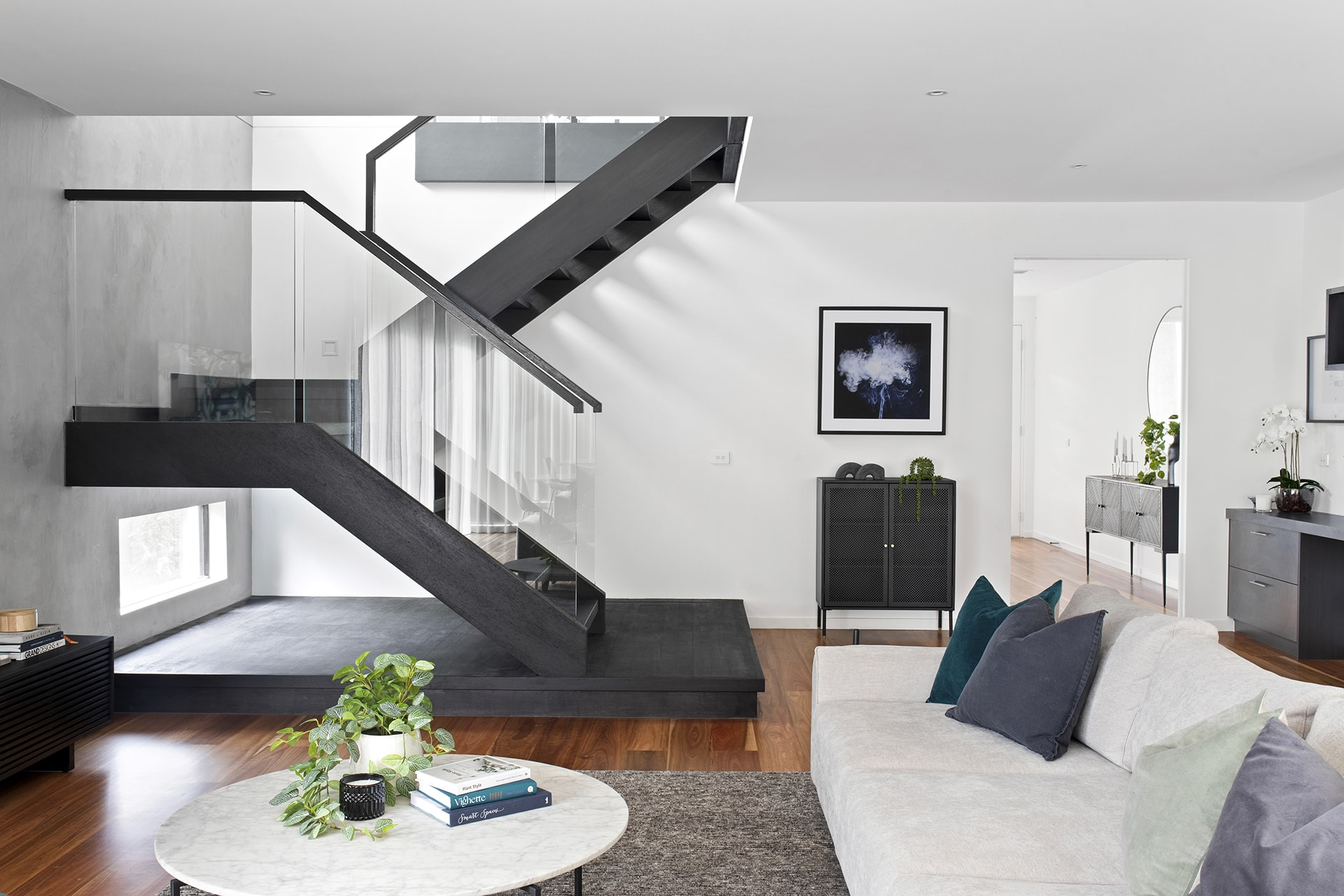 open plan living room with dark staircase glass balistrade and concrete feature wall dulux