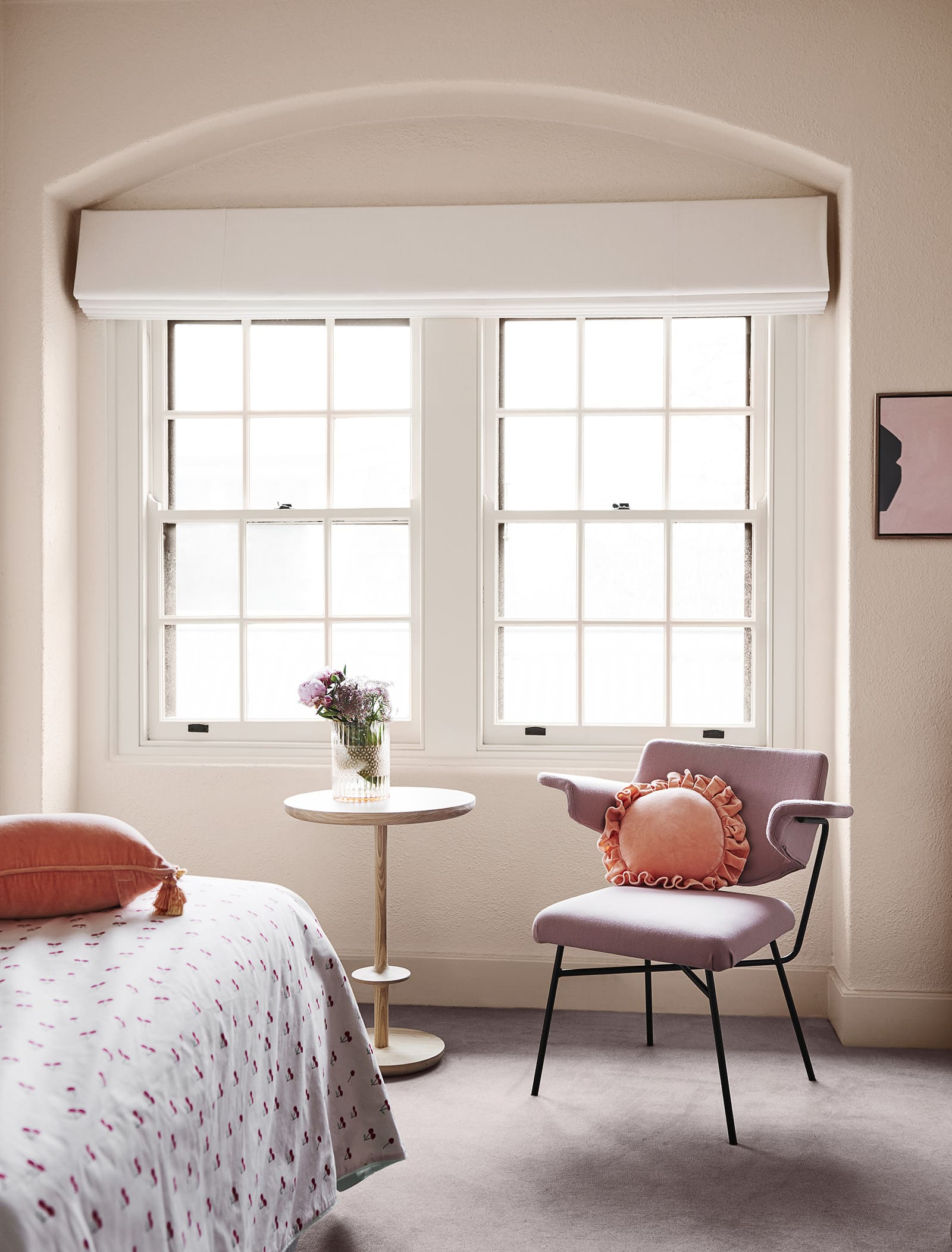 pale apricot bedroom with bay with traditional window frame and pink chair