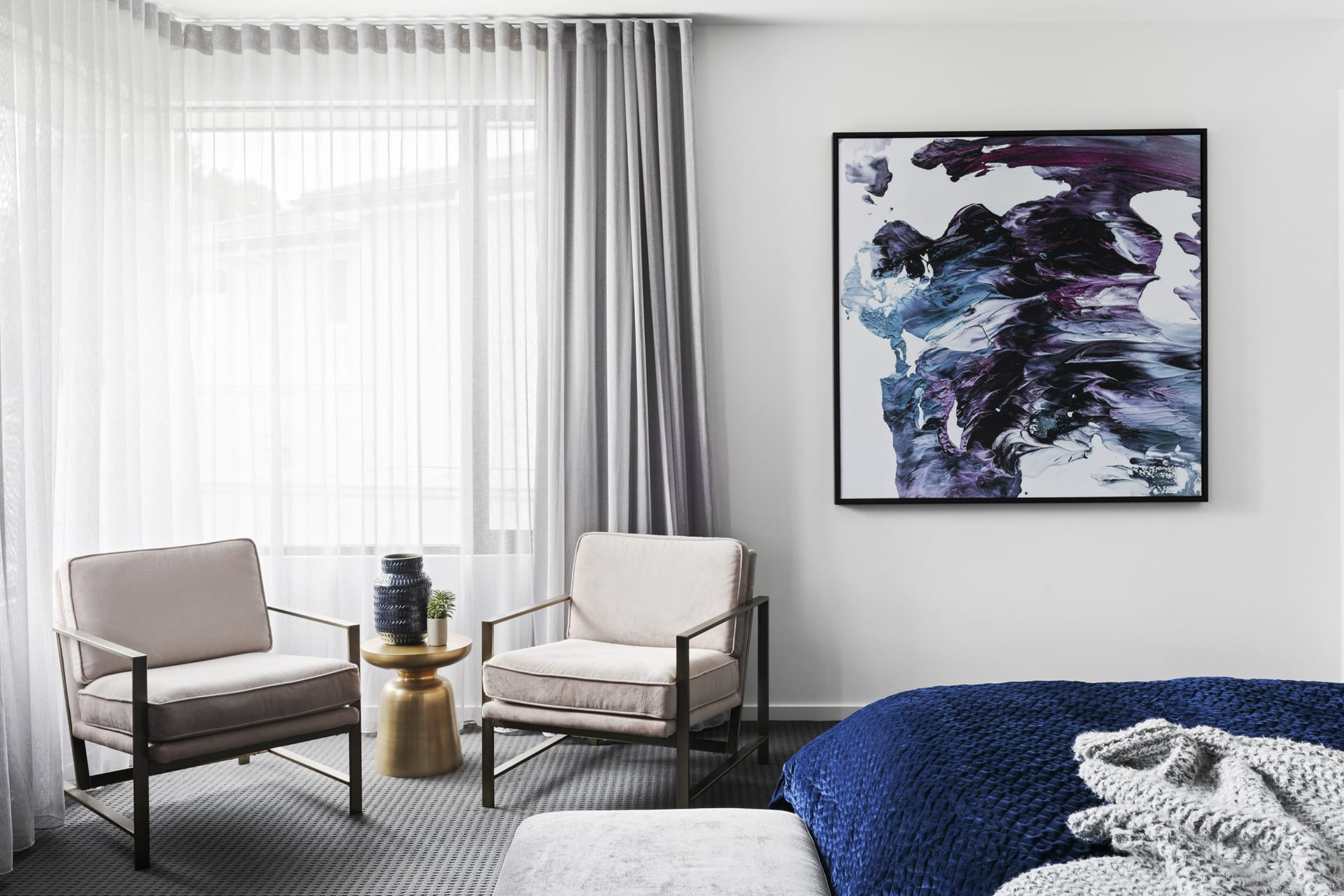 west elm pink velvet armchairs with bronze side table and large abstract artwork in master bedroom