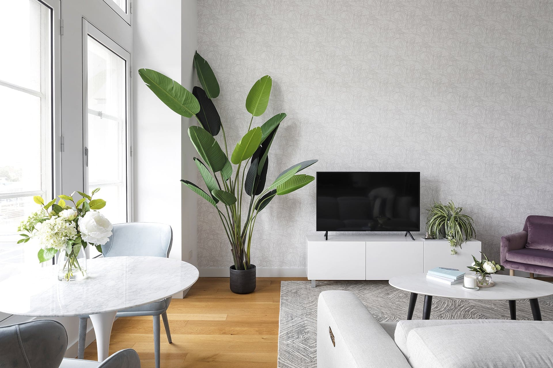 white and grey wallpaper design in melbourne apartment living room with large fake bird of paradise plant