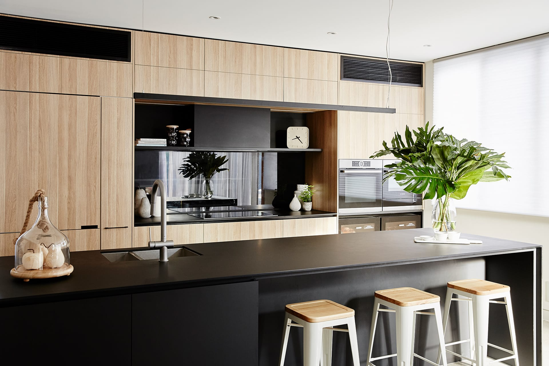 black kitchen with oak cabinetry and tinted mirror splashback property styling melbourne