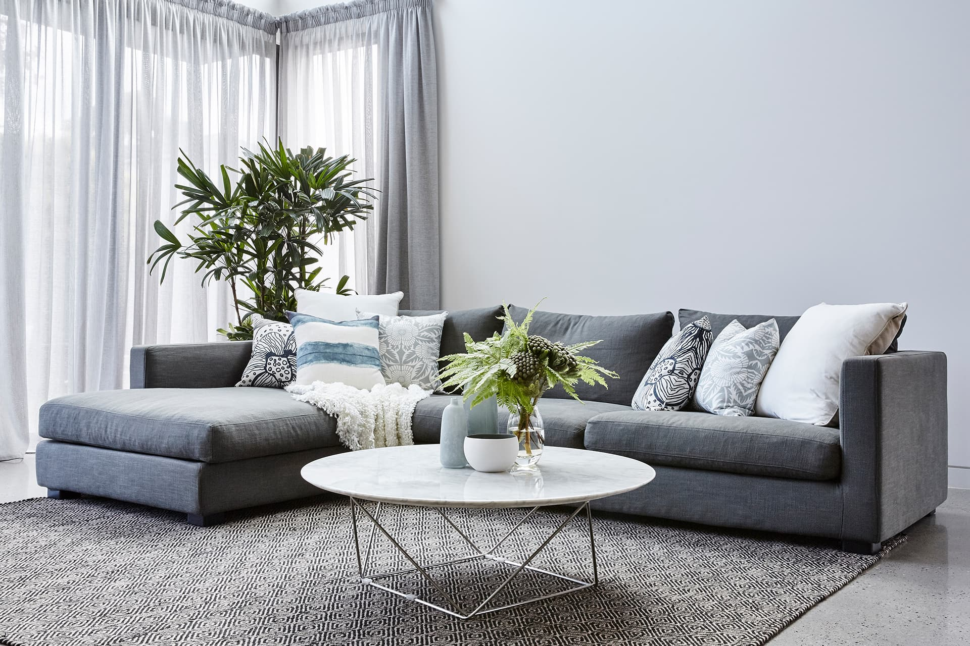 luxe coastal living room with polished concrete floor and globewest sofa by property styling melbourne