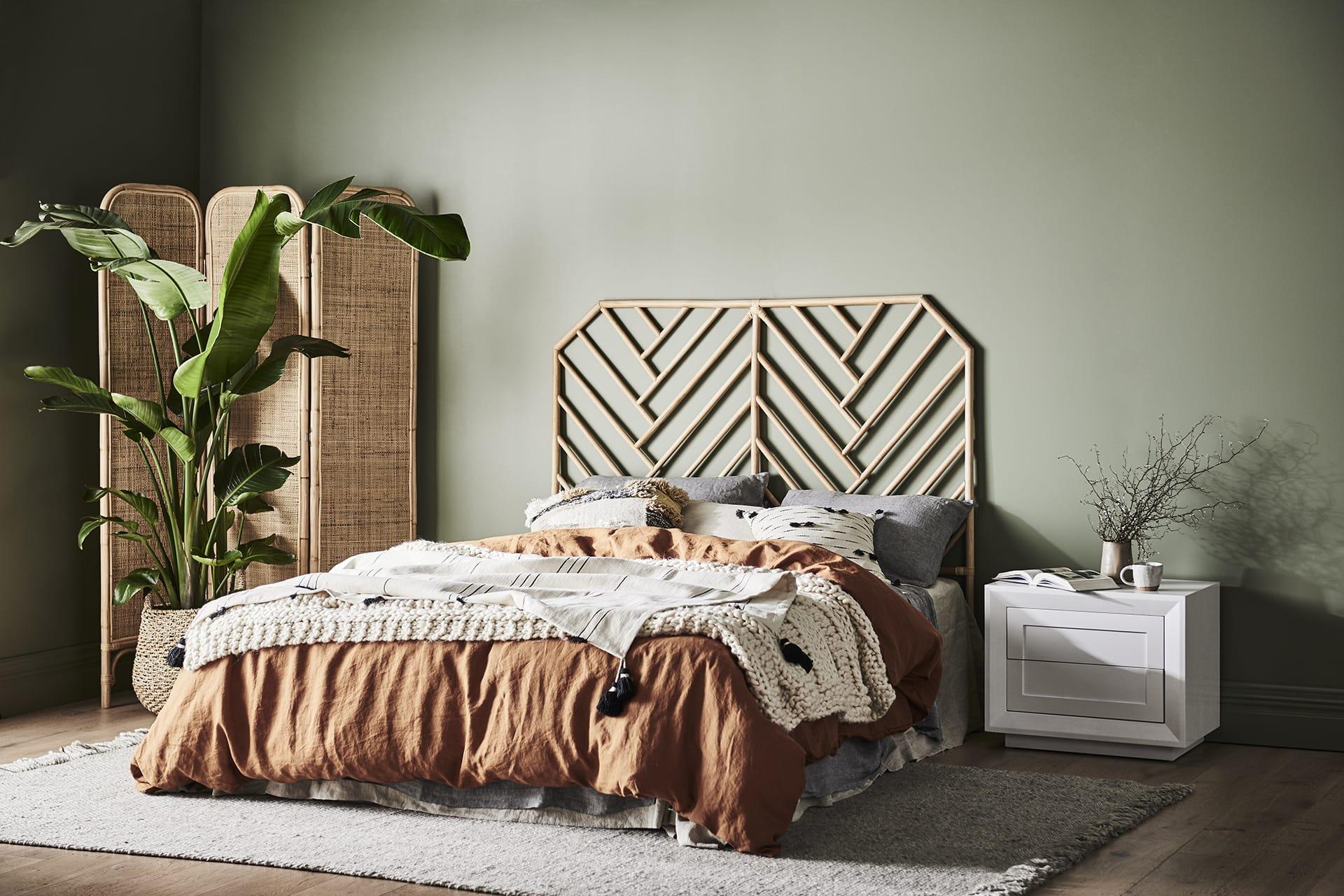 boho luxe bedroom wicker headboard and cane screen in green bedroom from globewest