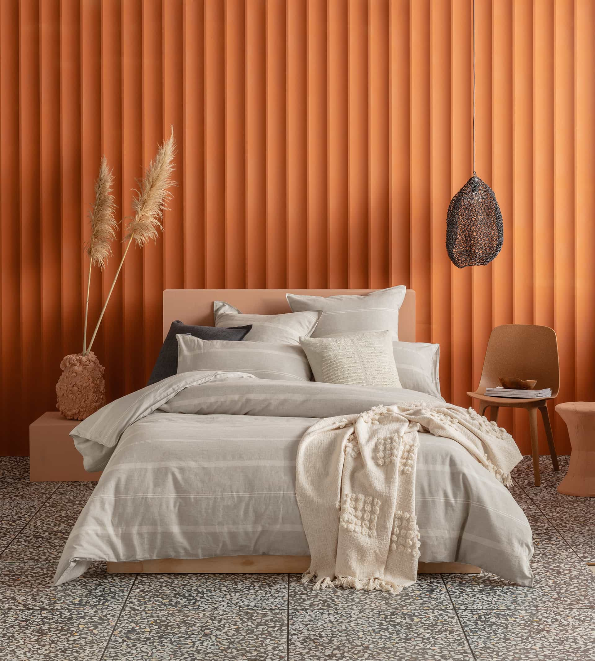 kas balmoral colourful quilt cover sets neutral bedding against orange feature wall