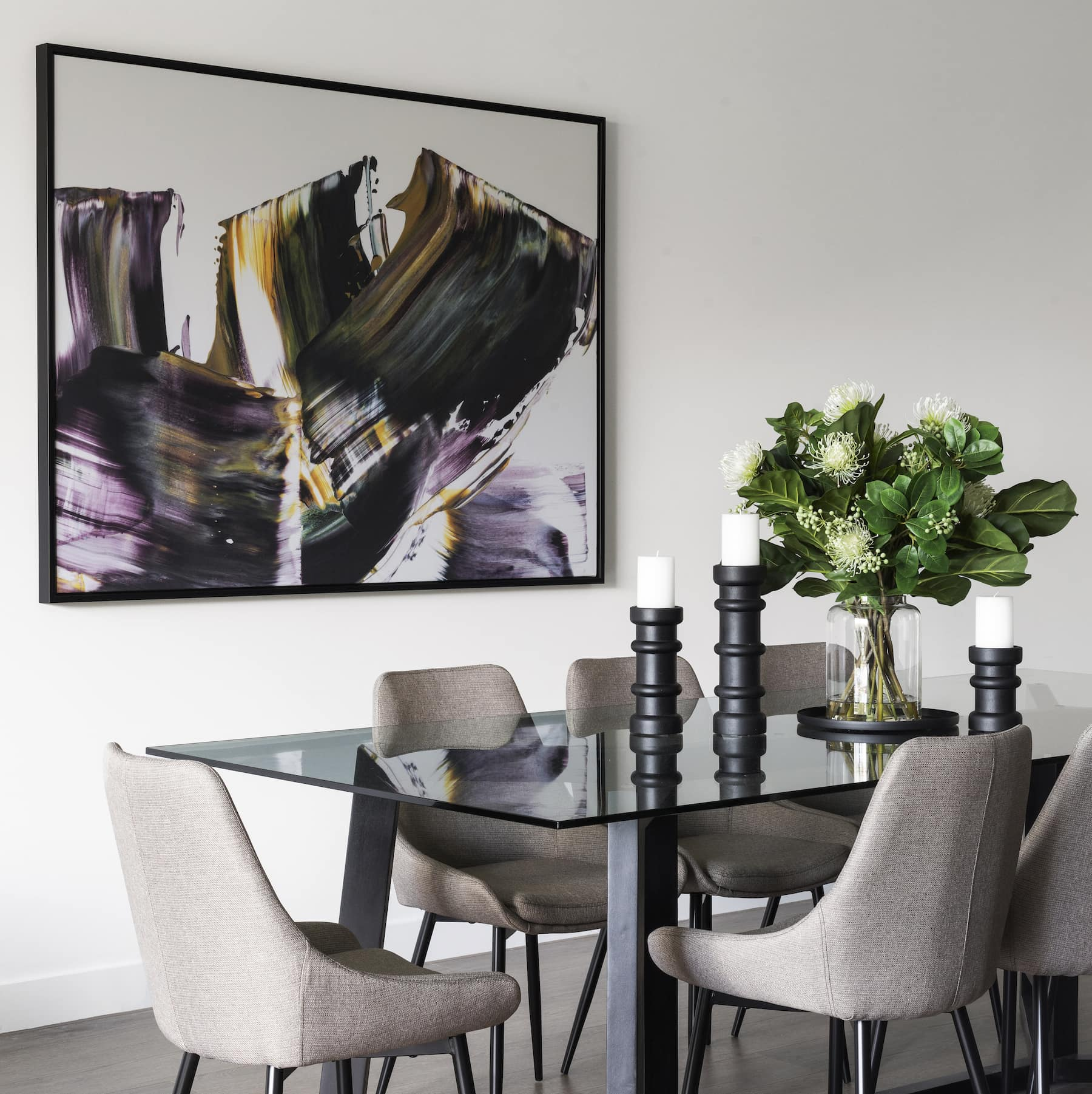 moody abstract art in dining room with glass top dining table and grey chairs