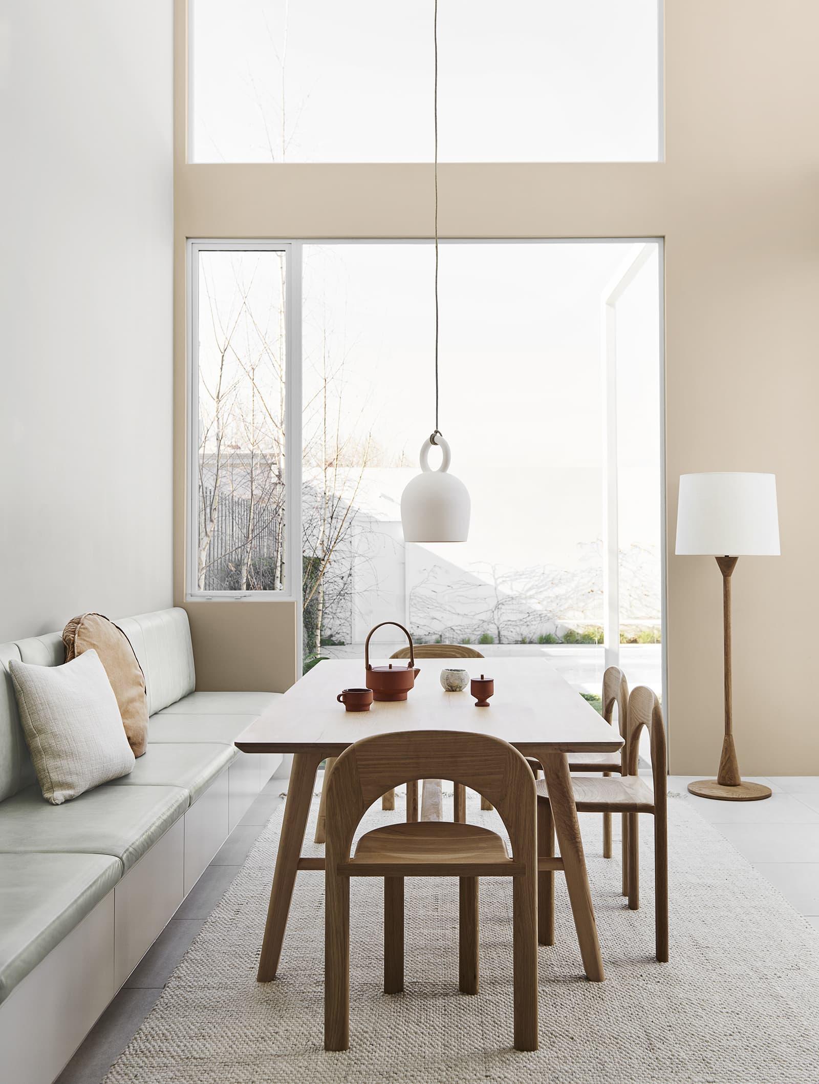 neutral interior design scheme dining room with concrete pendant light over light oak dining table