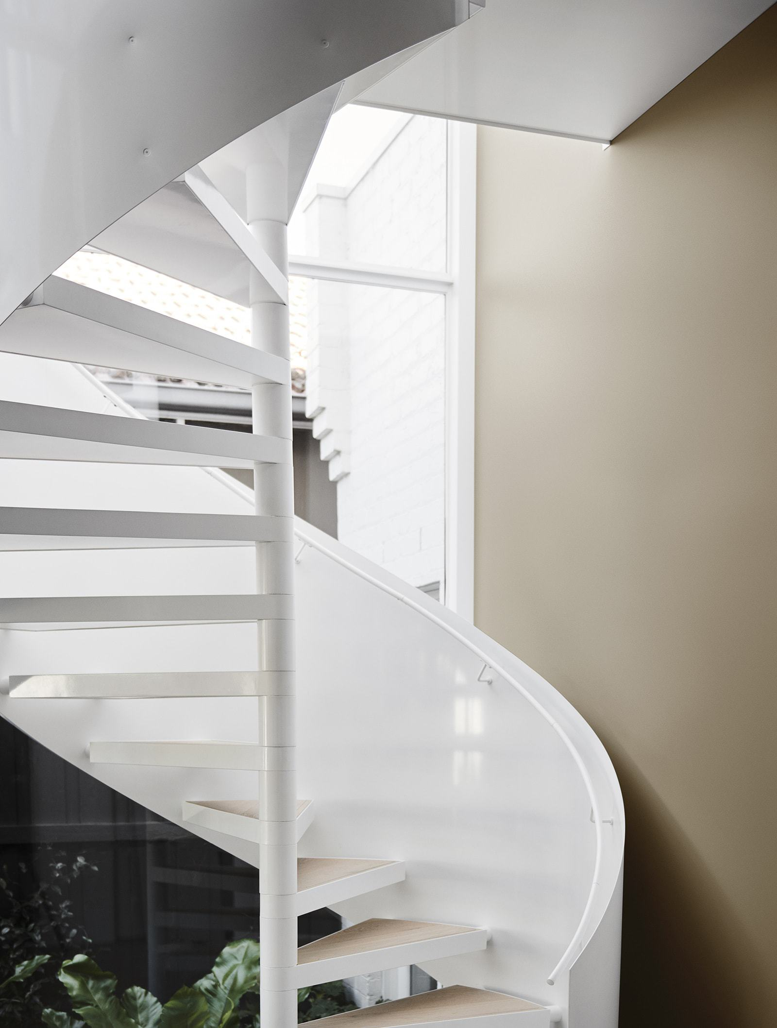 neutral interior design scheme white staircase against muddy terracotta wall paint