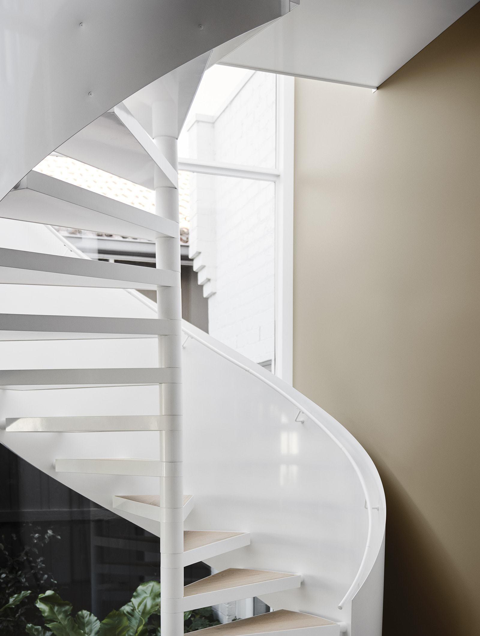 neutral interior design scheme white staircase against muddy terracotta wall paint