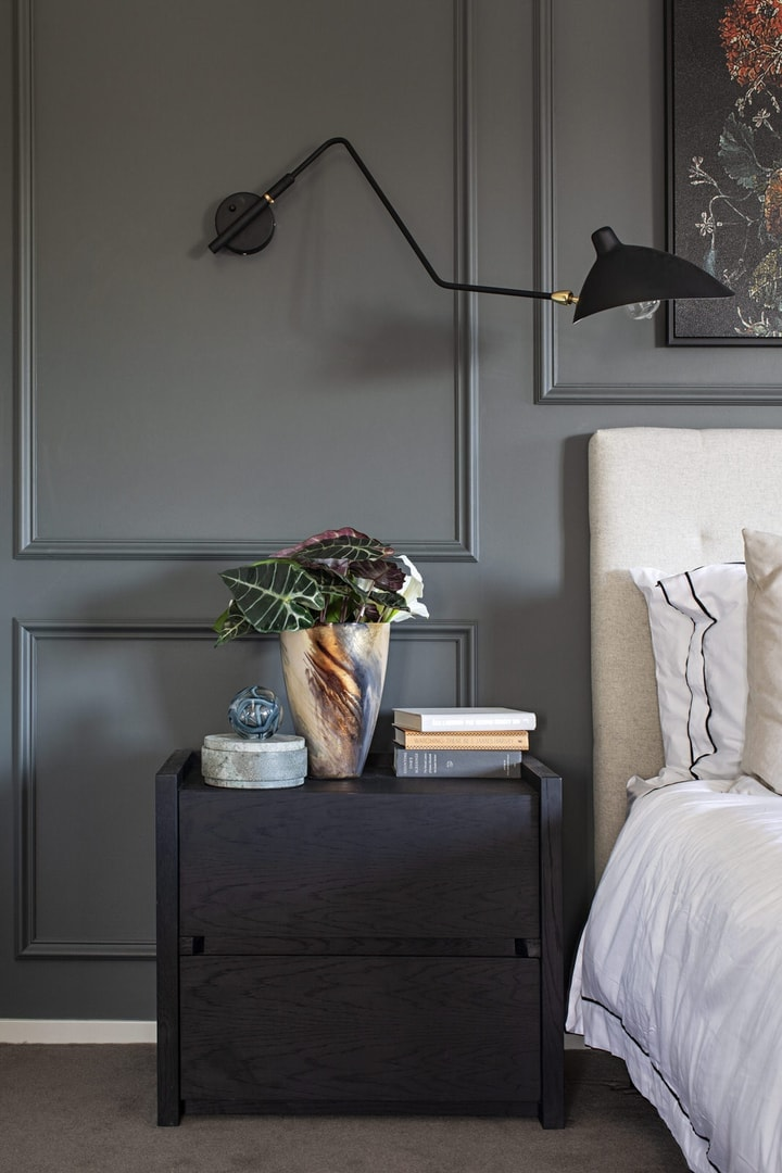 bedside table styling on dark brown side table with flowers and black wall sconce