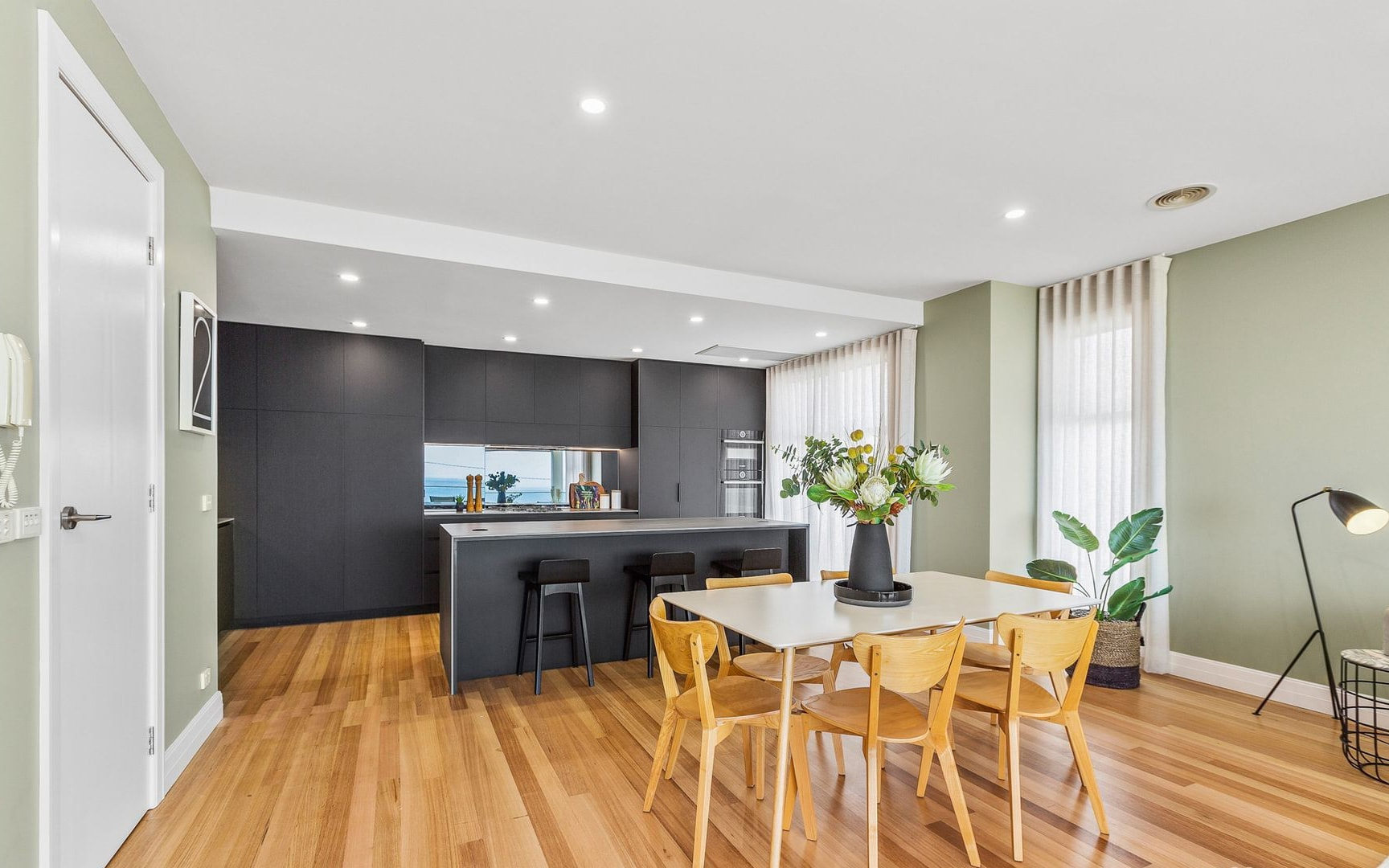 black industrial kitchen with concrete slab in coastal house with oak parquet