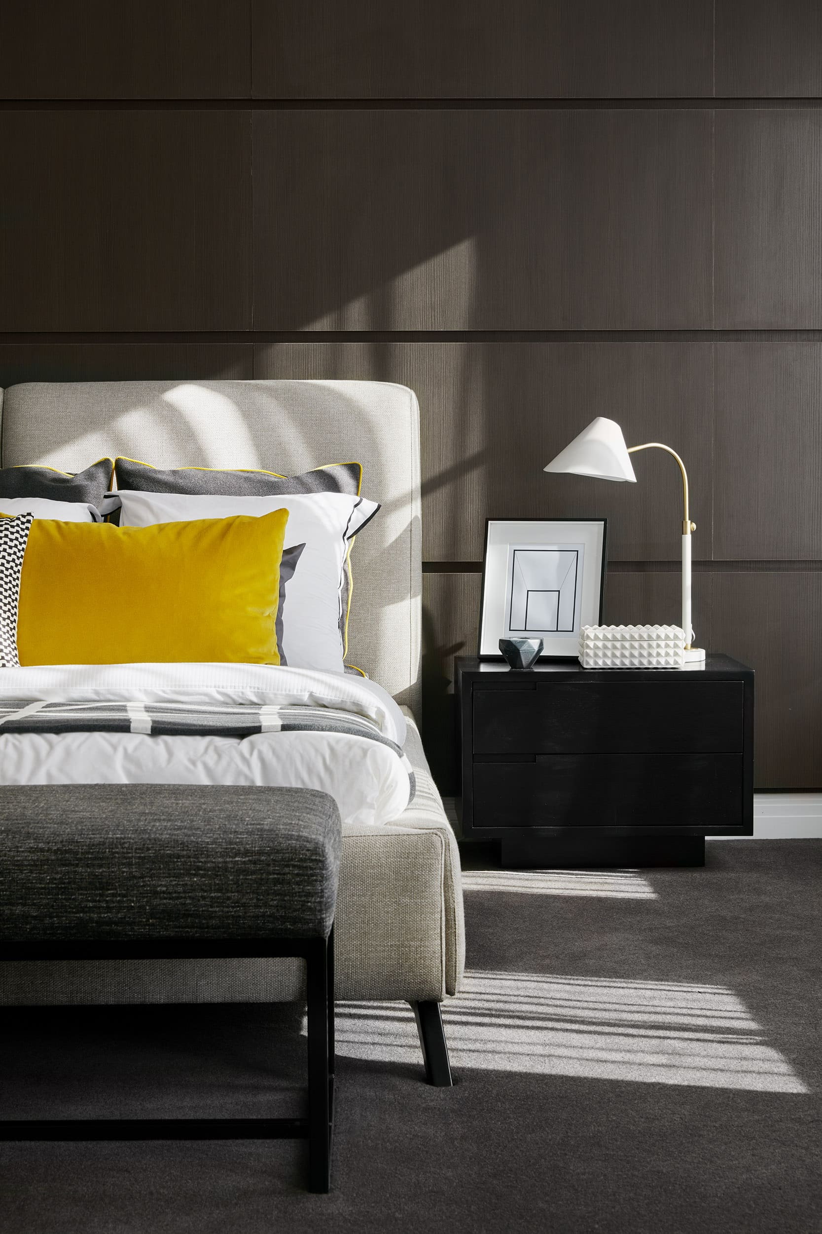 dark brown timber bedroom feature wall grey upholstered bed with mustard cushion