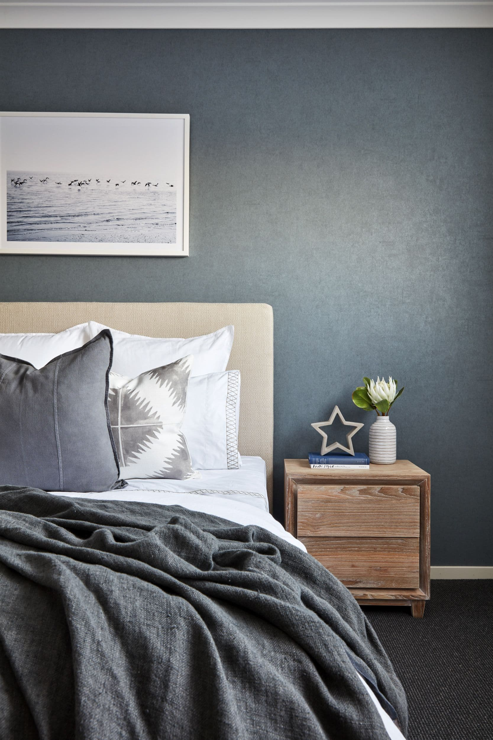 dark coastal bedroom with grey suede paint effect and coastal artwork with white frame