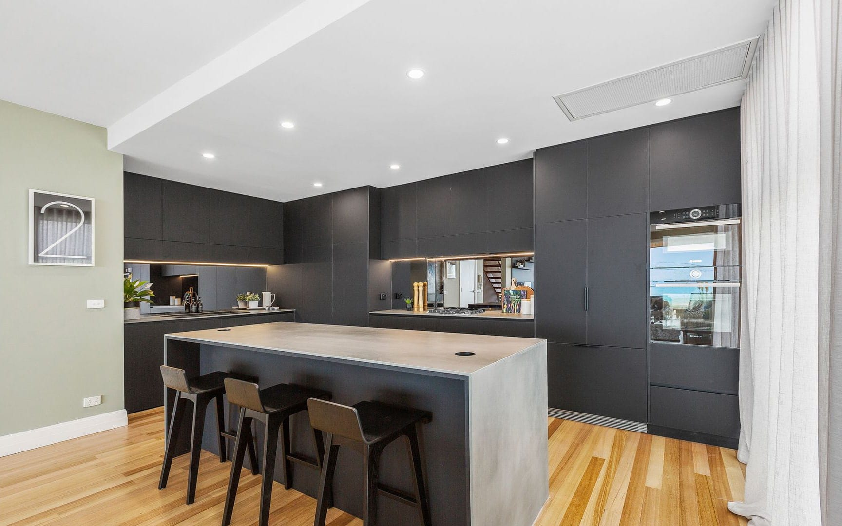 industrial kitchen design with black laminex cabinetry grey stone countertops and tinted glass splashback