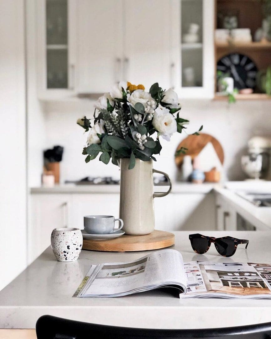 kitchen bench vignette with tall vase and round timber tray