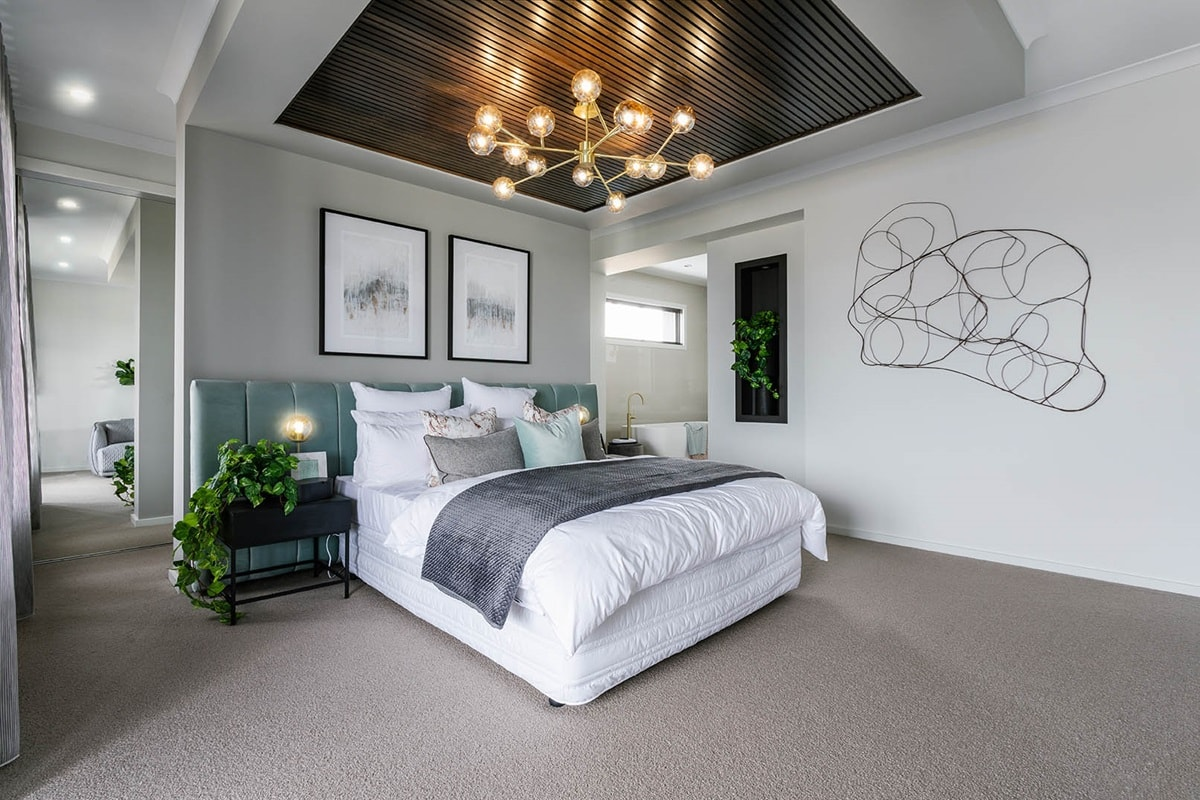 master bedroom with timber root panels and feature light above bed green oversized velvet headboard