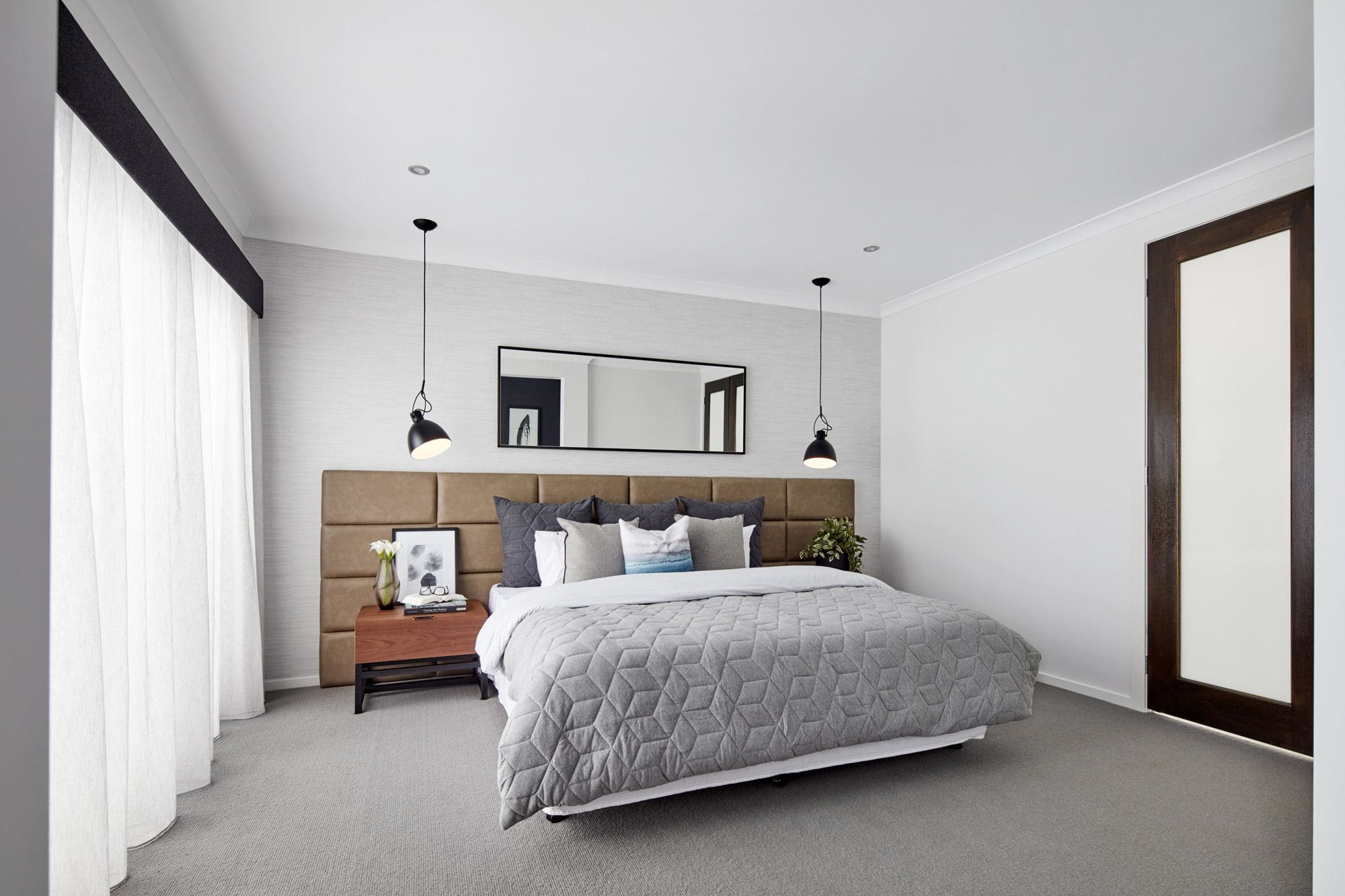 oversized brown leather headboard in masculine modern bedroom with grey bedding