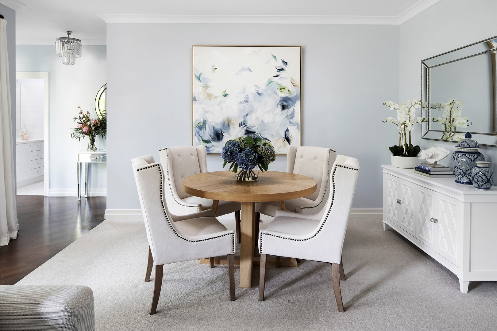 classic hamptons interior design dining room with chalie macrae art on light blue wall