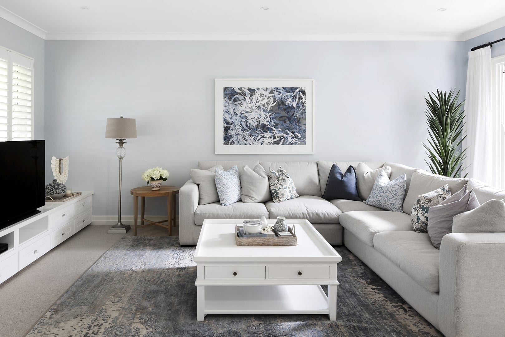 classic hamptons interior design scheme living room with light blue walls and cream sectional sofa