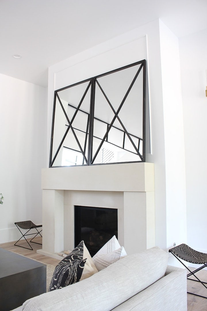 grid of mirrors leaning on mantle over fireplace