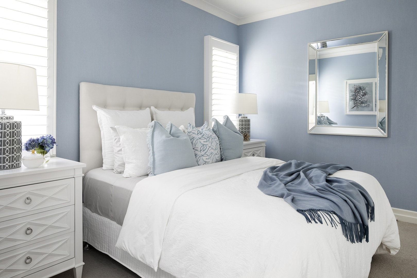 hamptons bedroom with light blue walls cream upholstered headboard and white hamptons bedside tables
