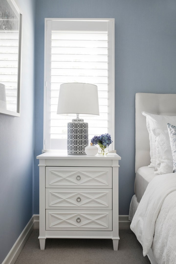 hamptons-bedroom-with-white-plantation-shutters-and-white-hamptons-bedside-table-blue-wallpaper