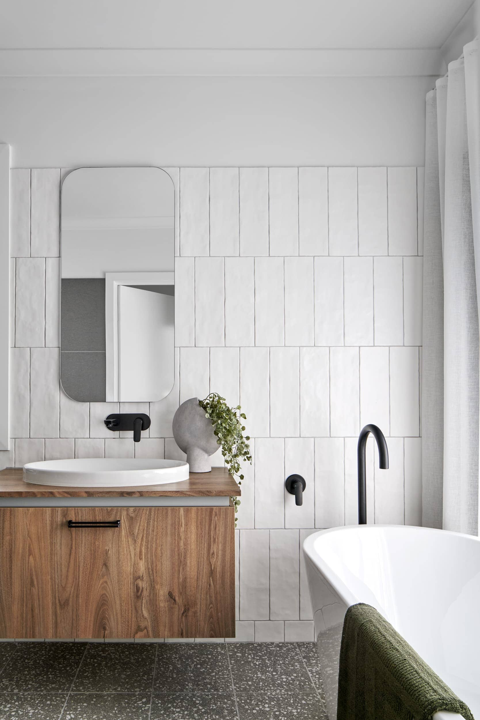 industrial style bathroom with matt black tapware and timber floating vanity