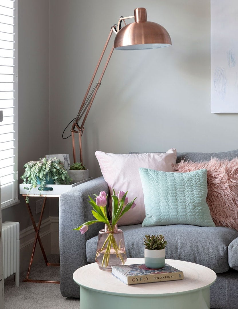 large copper floor lamp in rental living room with turquoise and pink cushions on grey sofa