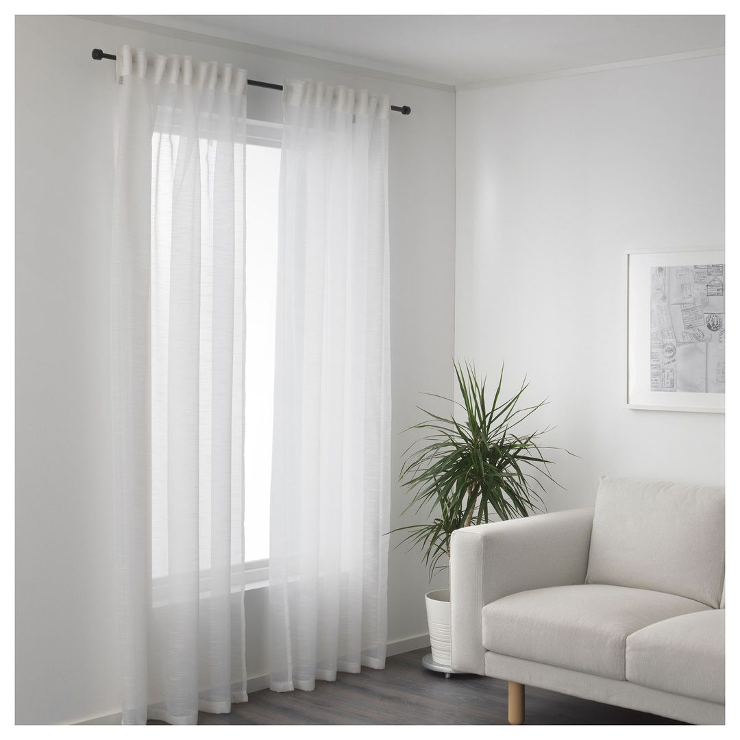 white ikea sheer curtains on black metal rod in living room