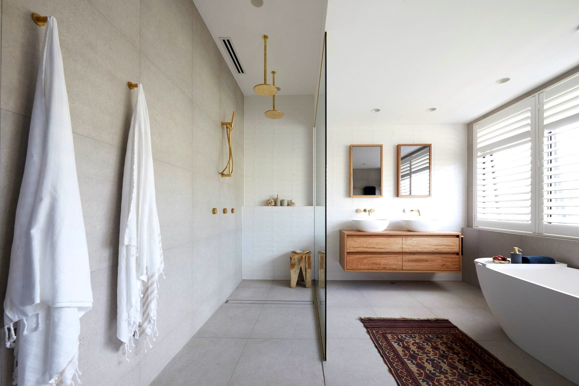 bathroom with large stone wall and floor tiles and walk in shower