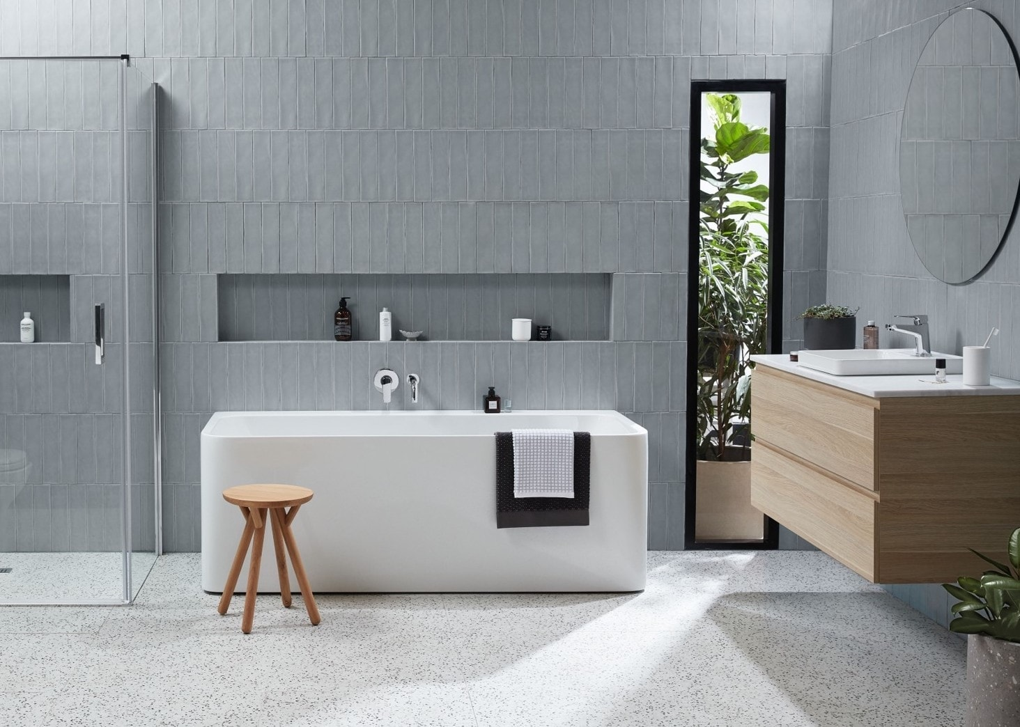 reece back to wall bath in grey tile bathroom with floating timber vanity