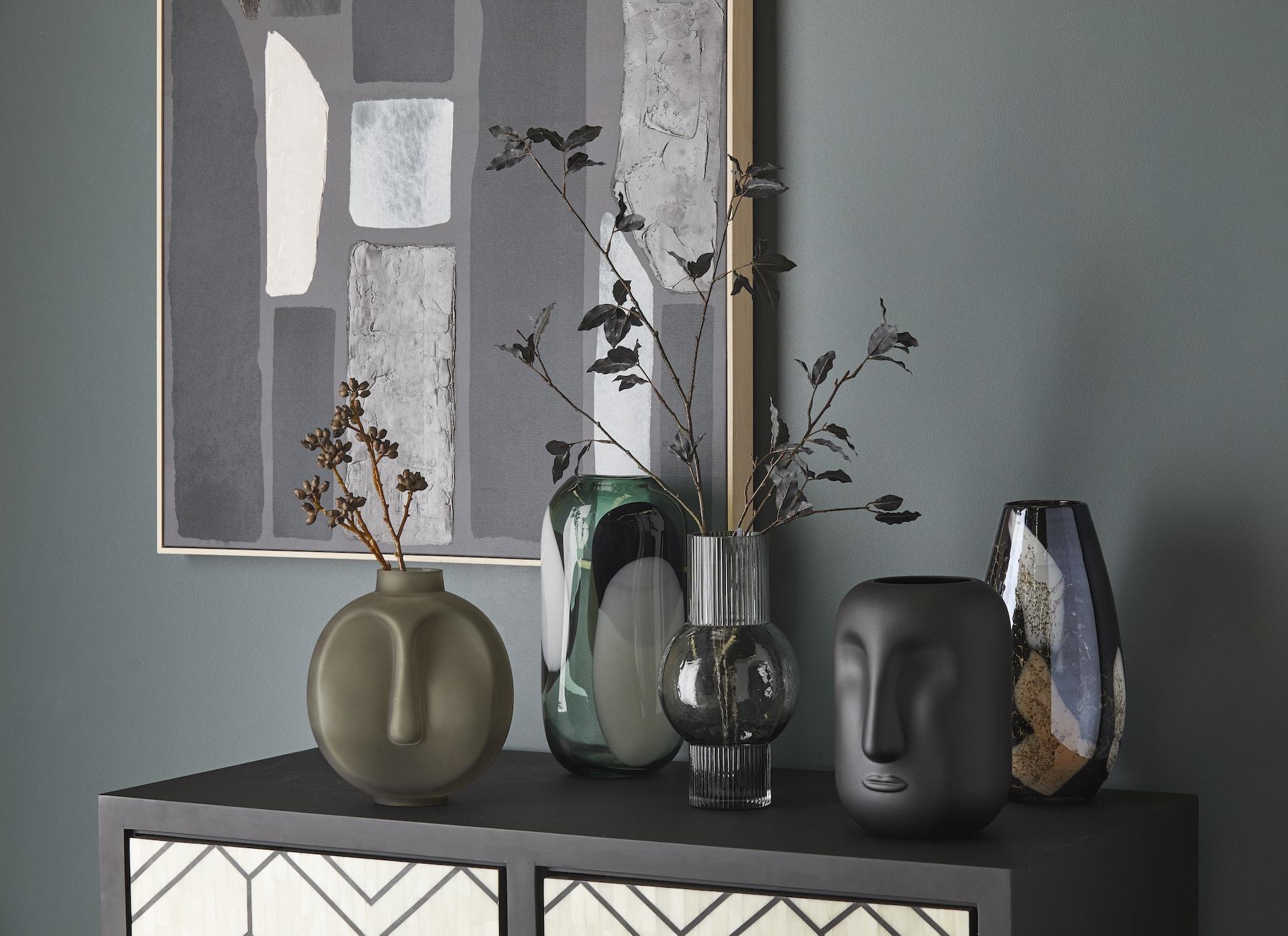 black and green figure vase face decor face vases on sideboard