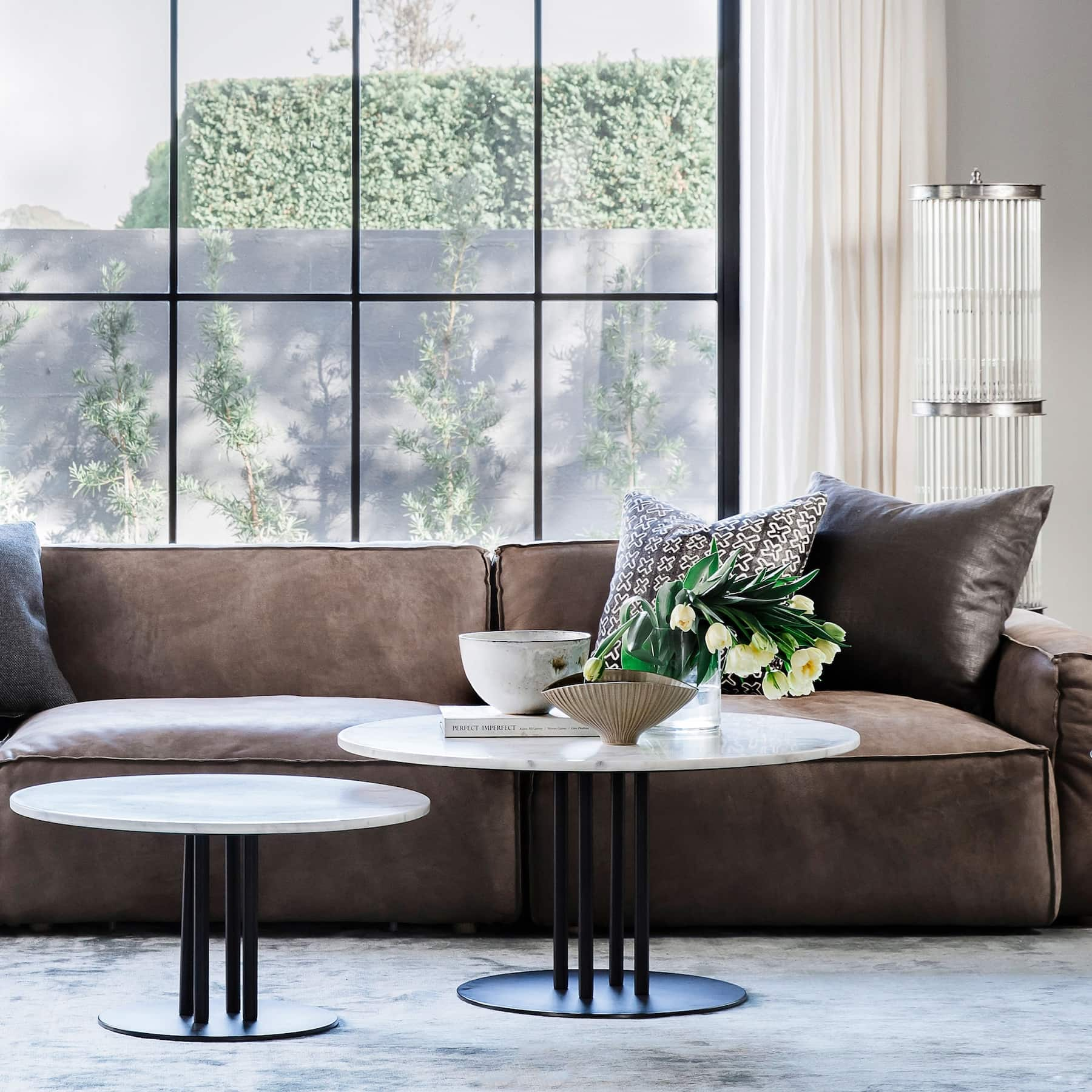 brown leather sofa with white round marble coffee table styling with flowers