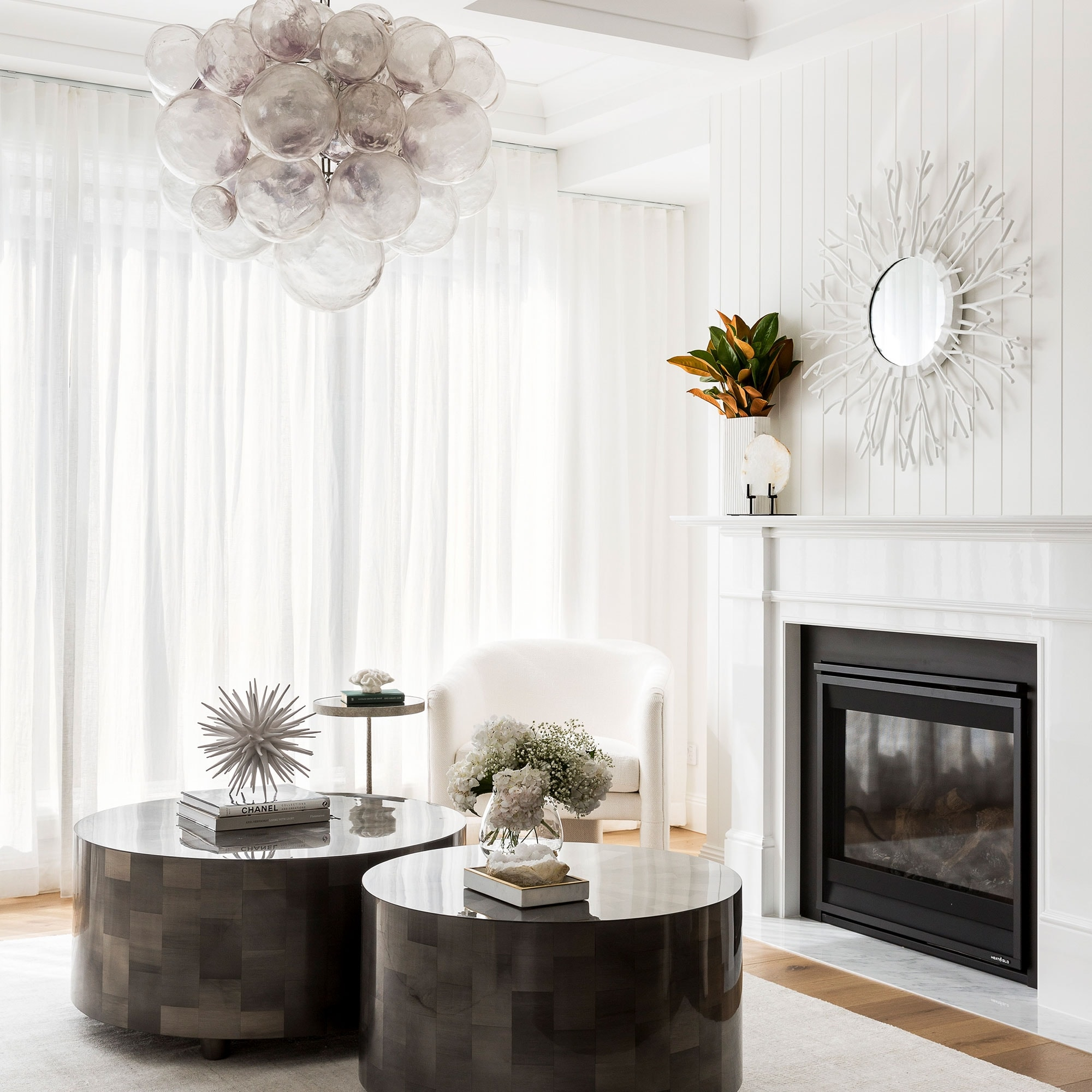 coco republic round coffee tables in white room with fireplace