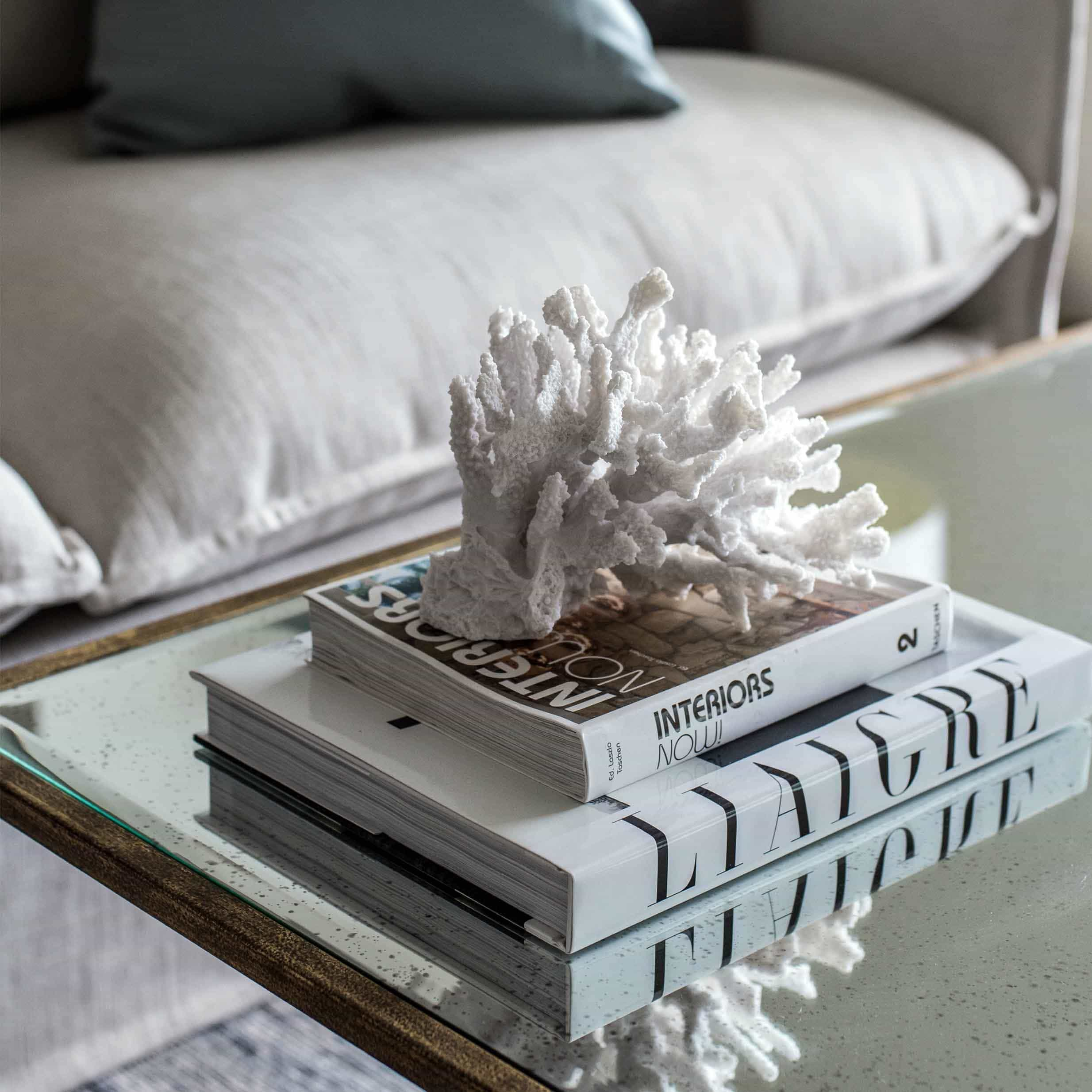 coco republic sinclair coffee table styling with stack of books and coral ornament