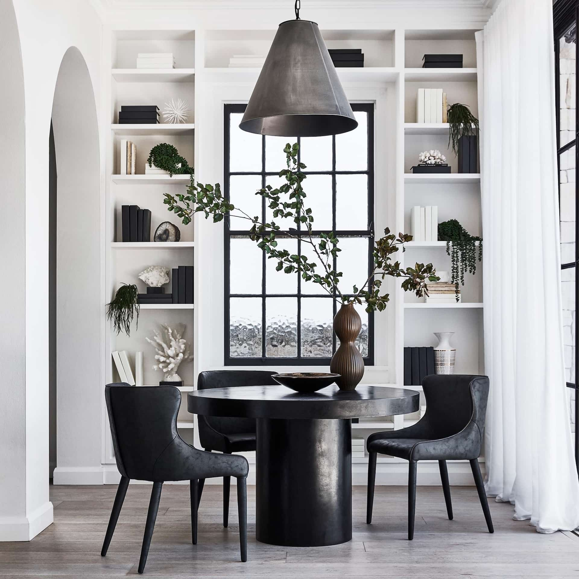 coco republic small round black dining table with pendant above it