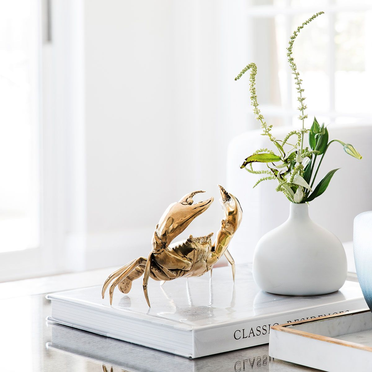 gold crab on white book coffee table styling coco republic